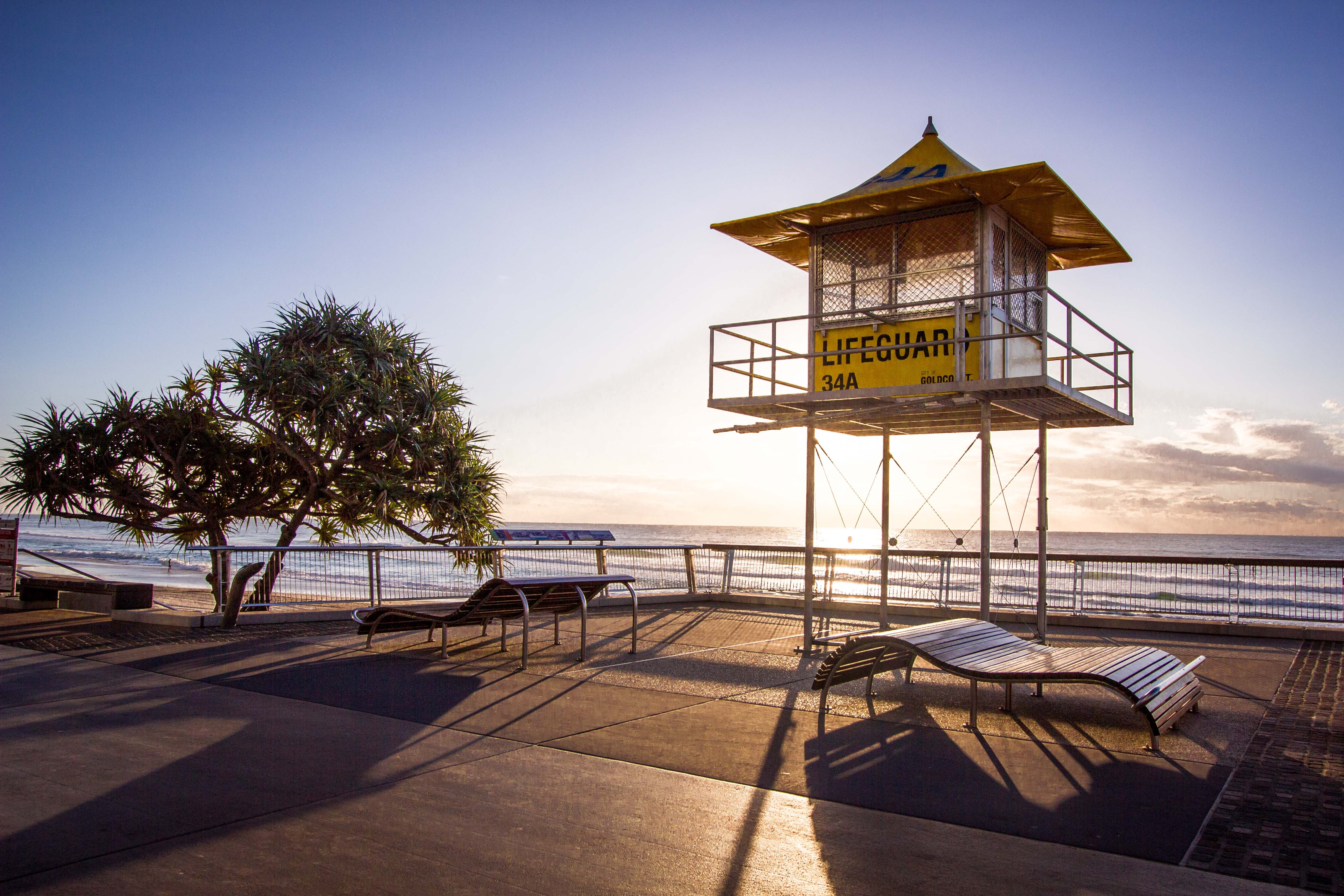 Lifeguard stand and tree cast shadows on the beachside promenade at Surfers Paradise during sunrise-or-sunset