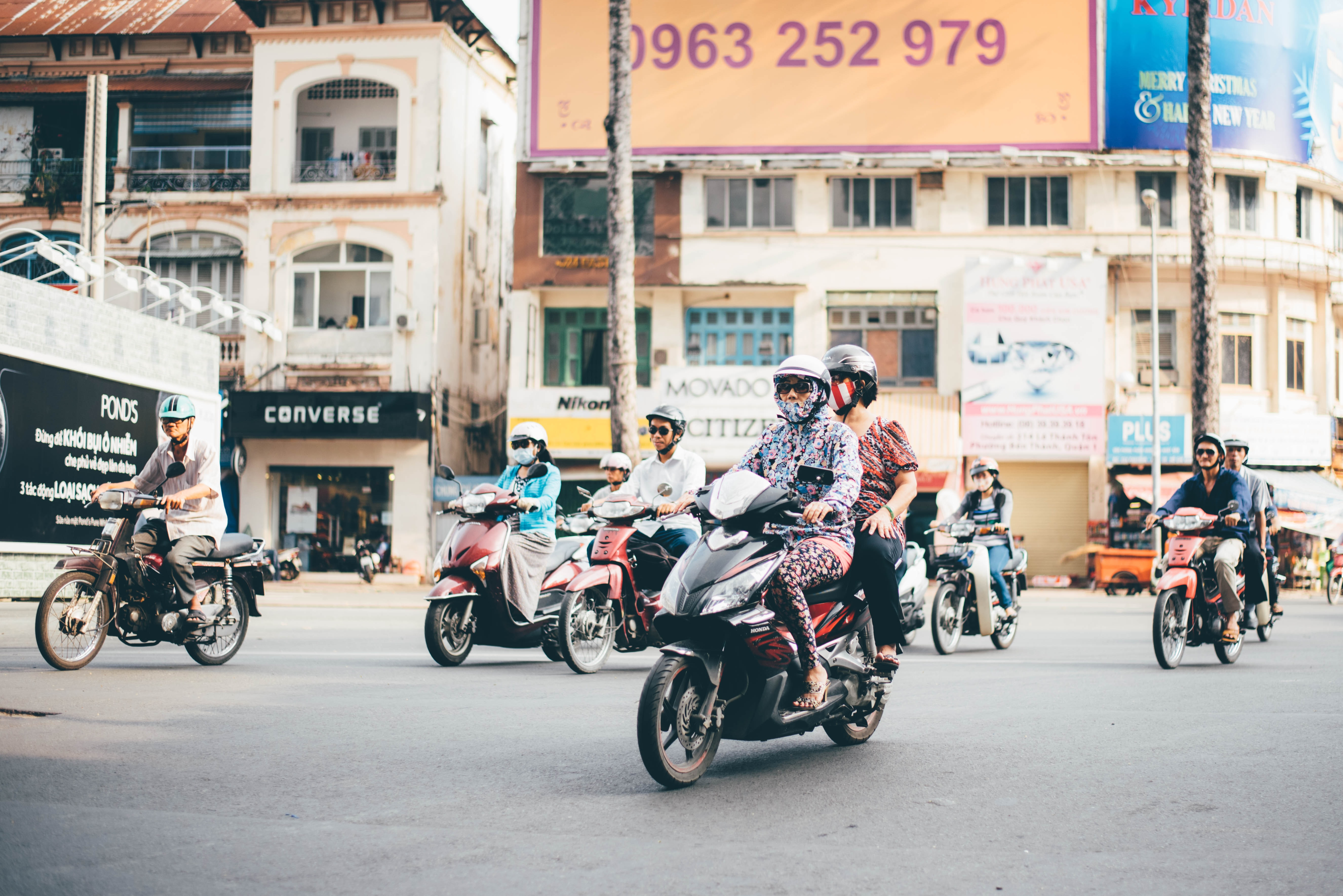 Diverse group of people riding vespas and motorcycles down a city street