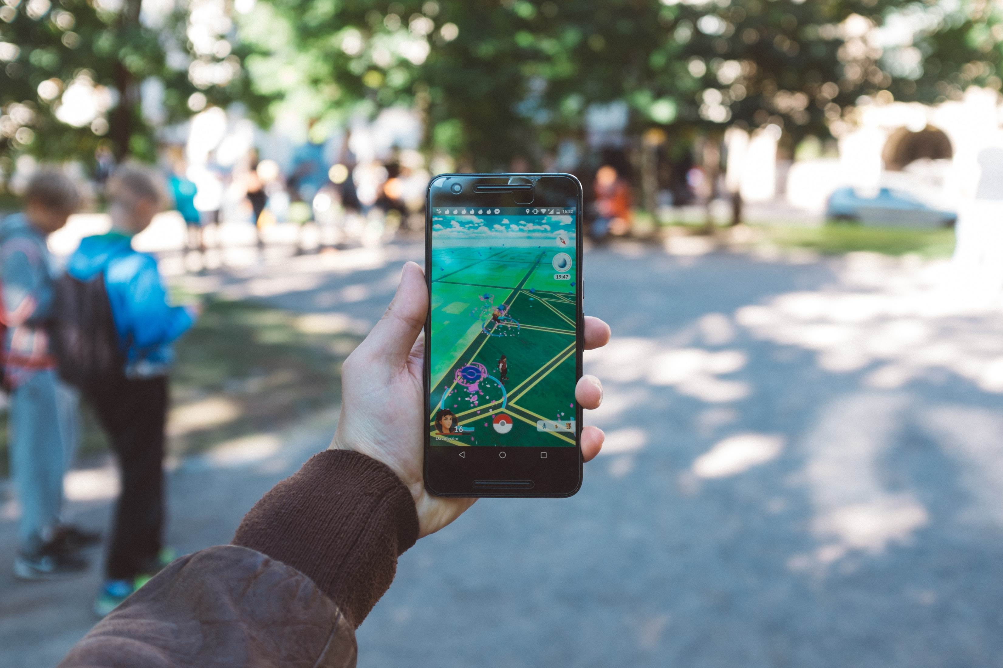 The mobile game, Pokemon GO, being played at a park