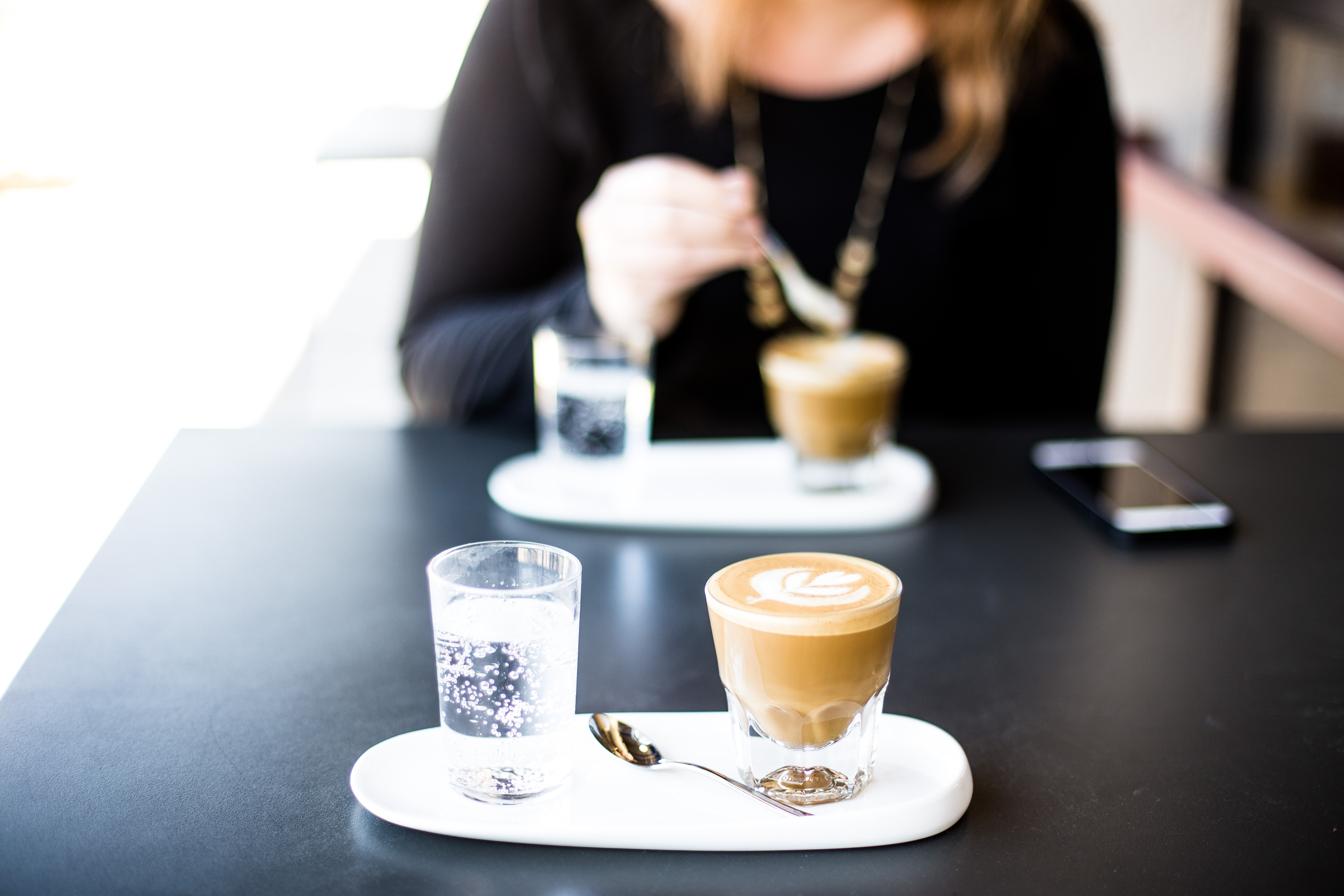 A woman sitting over a cup of coffee with another cup of coffee on the other side of the table