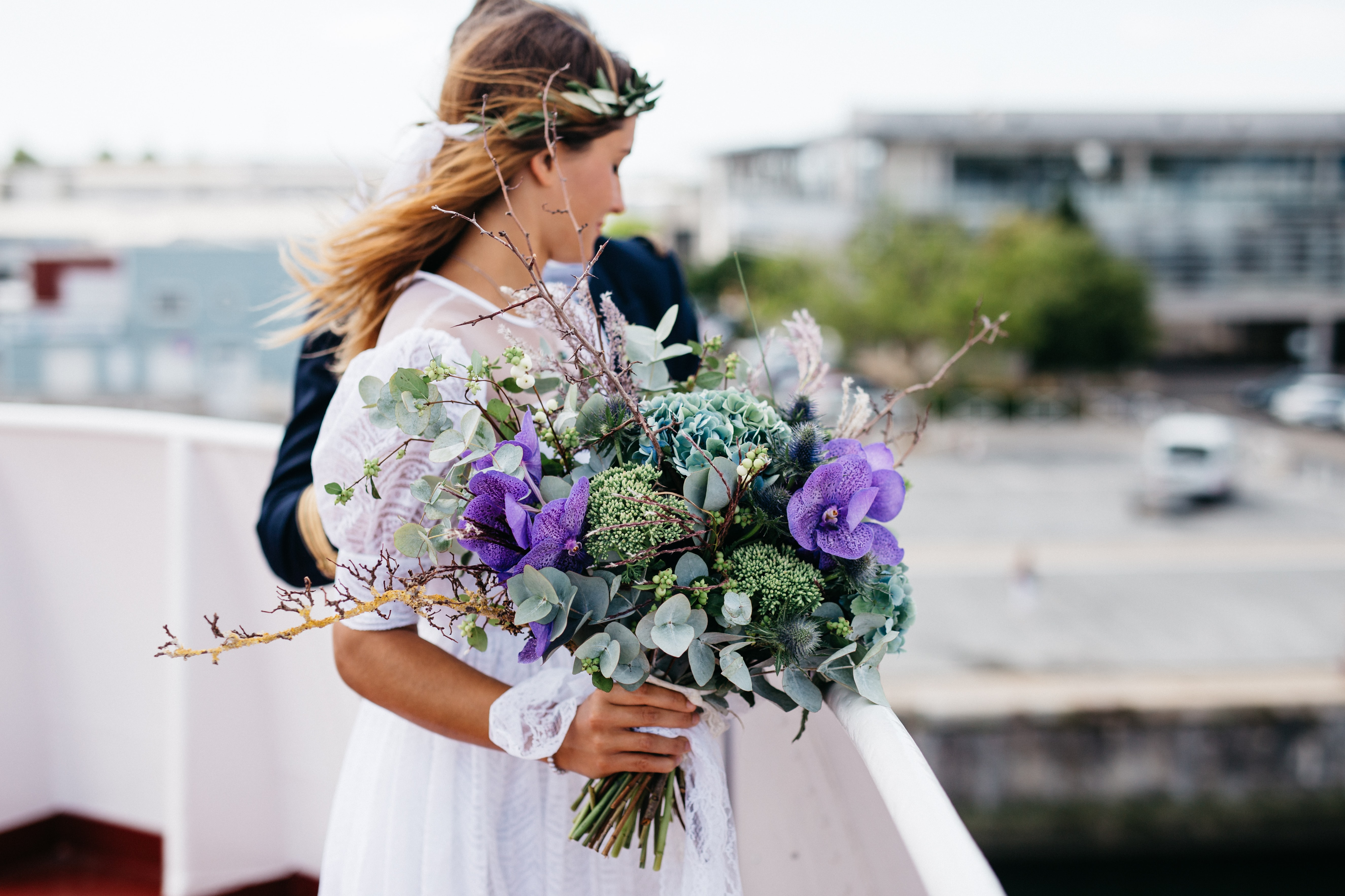 Just-married couple at an overlook in Musée Maritime de La Rochelle with an ornate bouquet