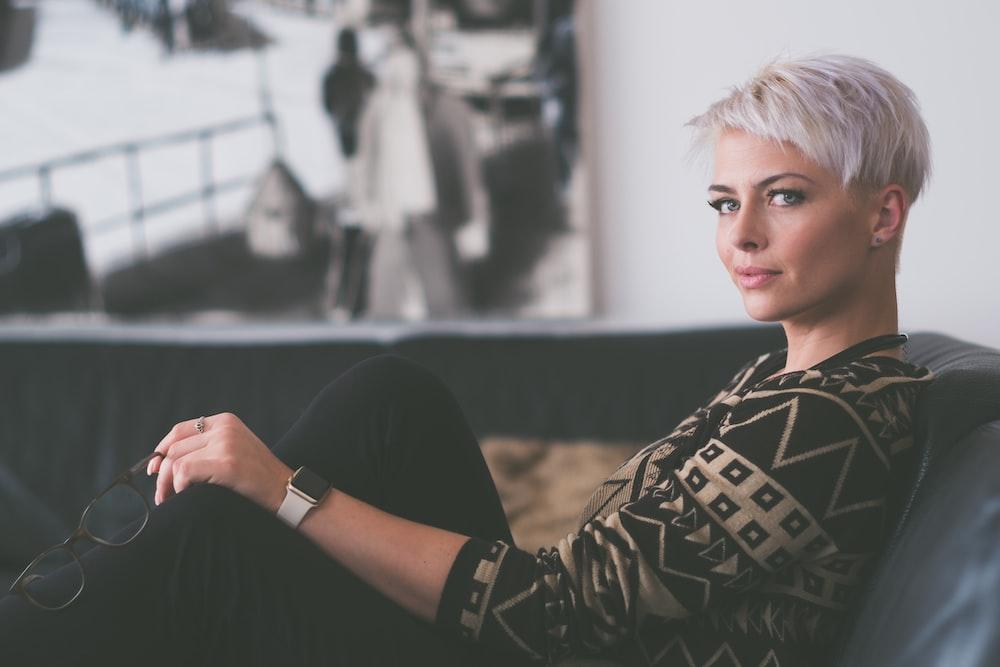 woman sitting on sofa holding eyeglasses