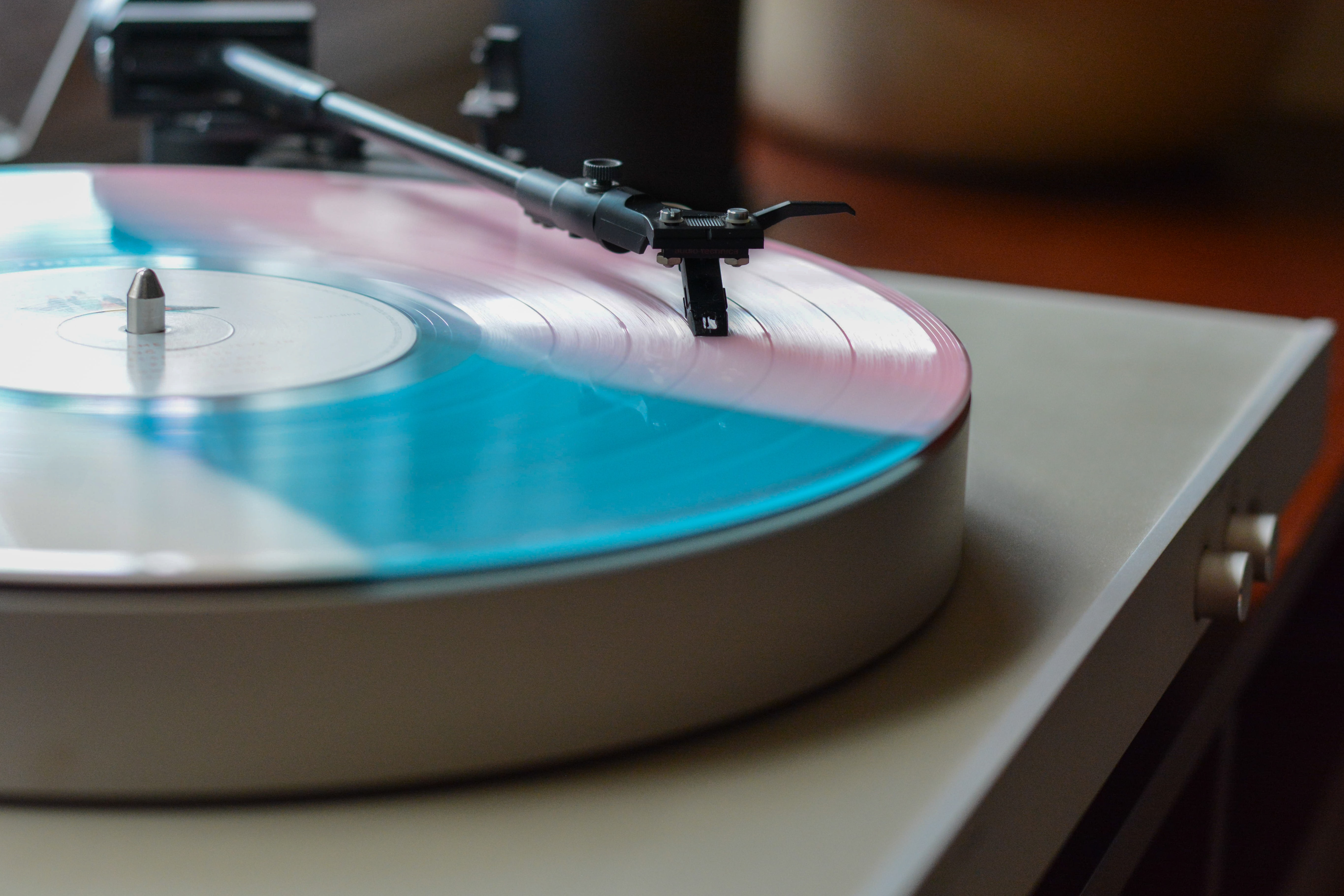 A close-up of a blue and pink vinyl on a turntable