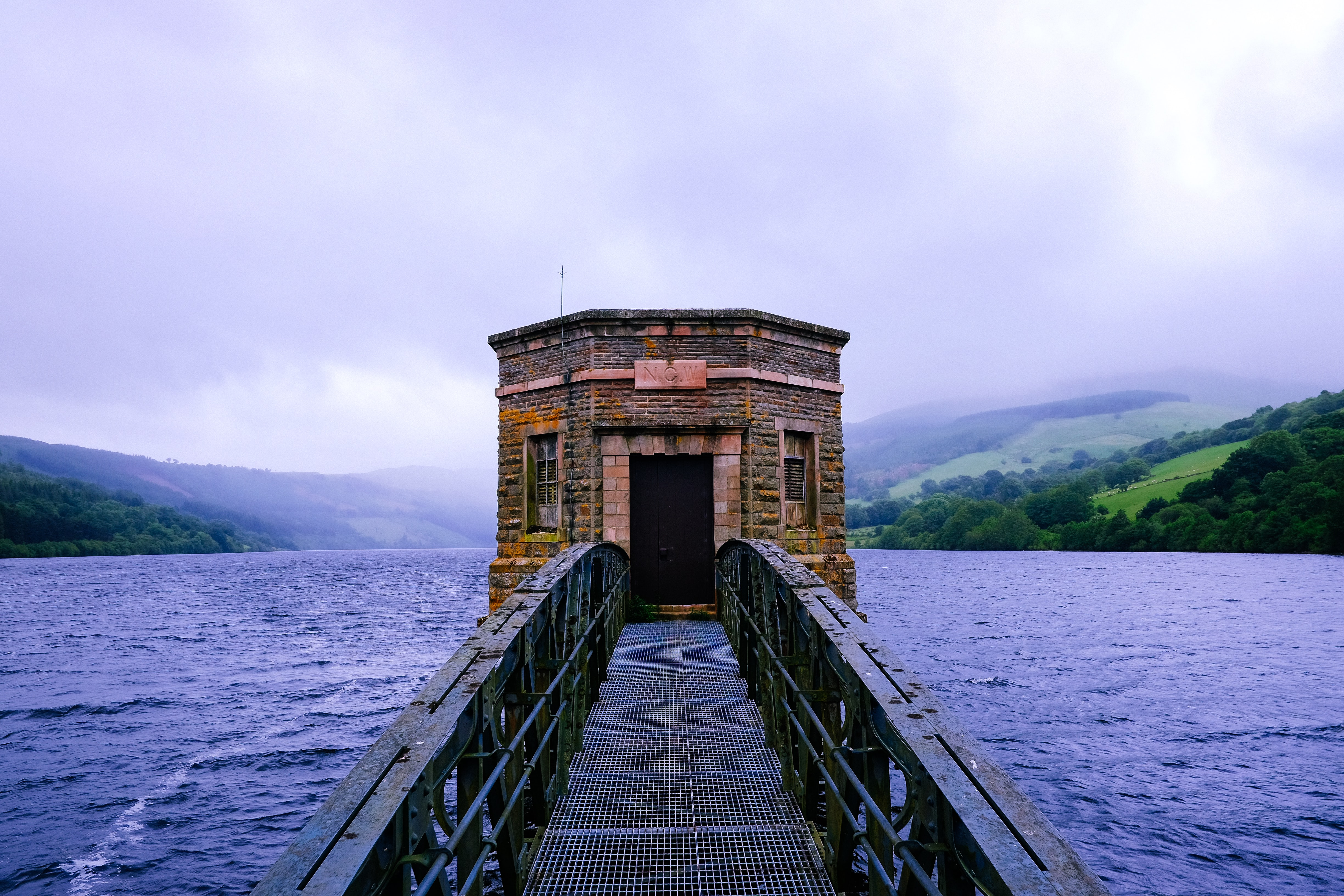 black metal bridge leading to building surrounded by water