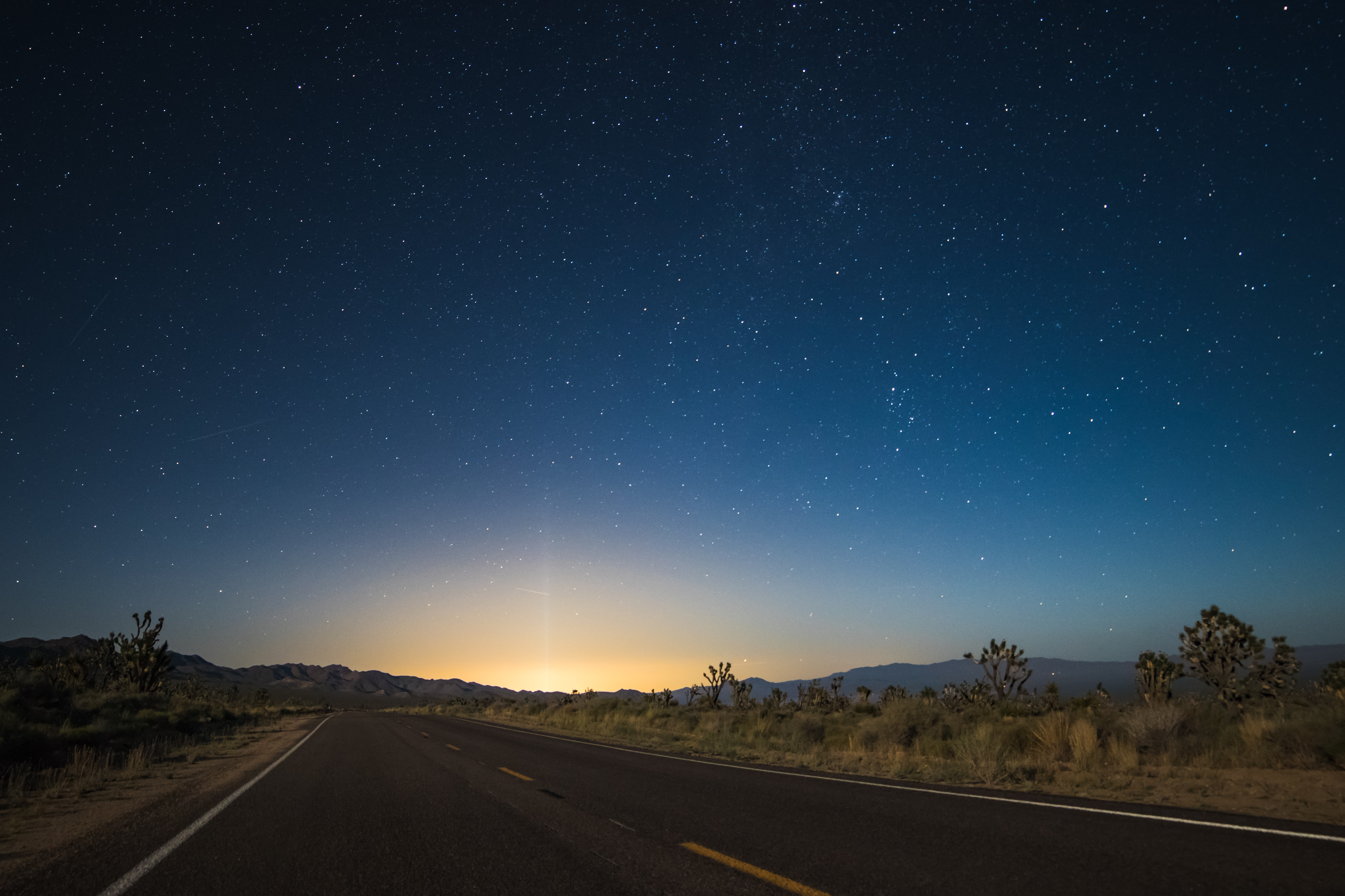 The pavement in the center of desert area leads to glowing sunrise illuminating night sky