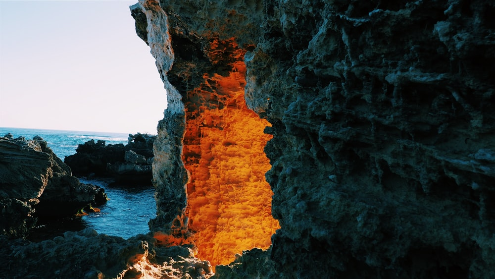 lighted cave entrance near body of water