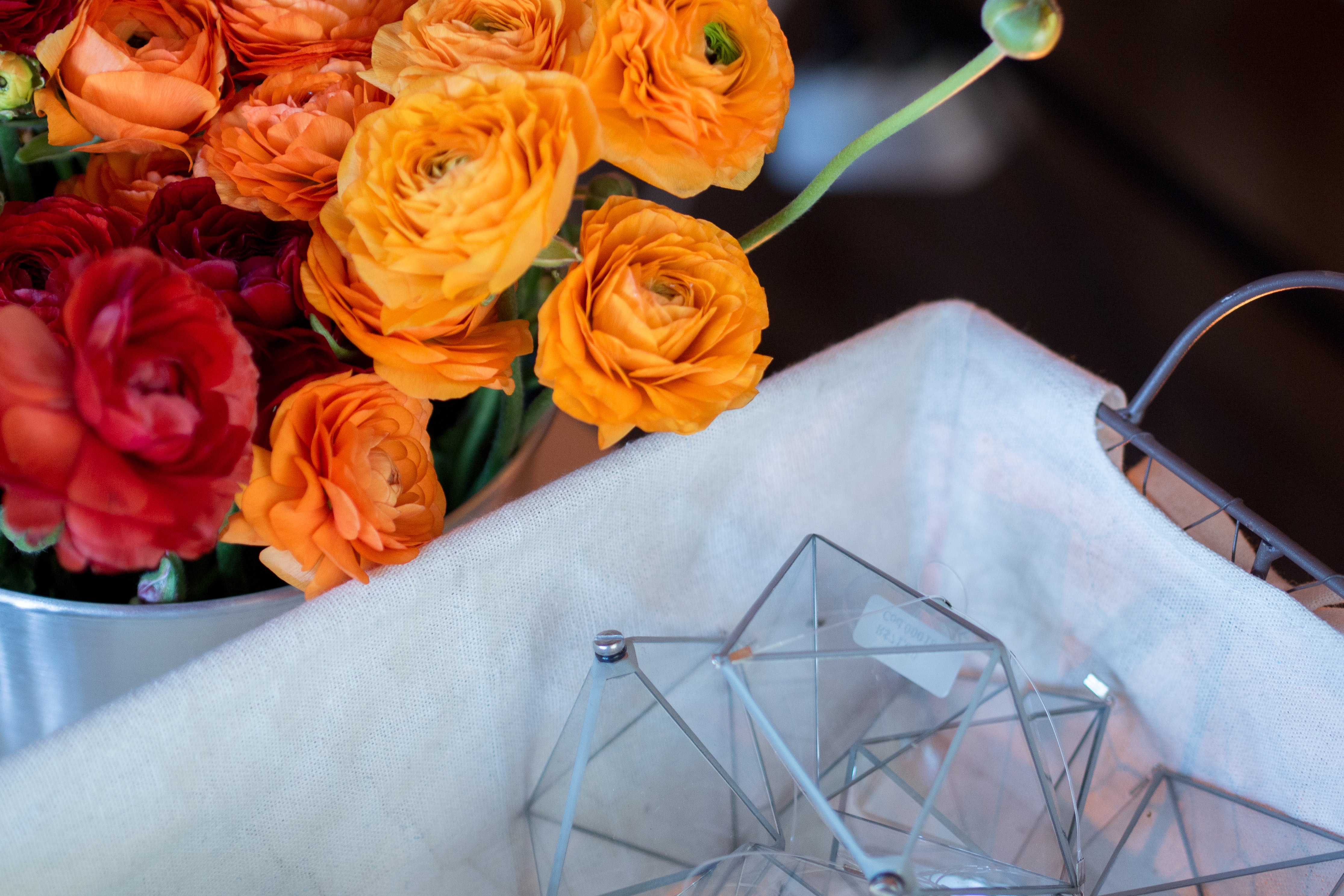 A large bouquet of red and orange roses in a bucket next to a basket with glass prisms