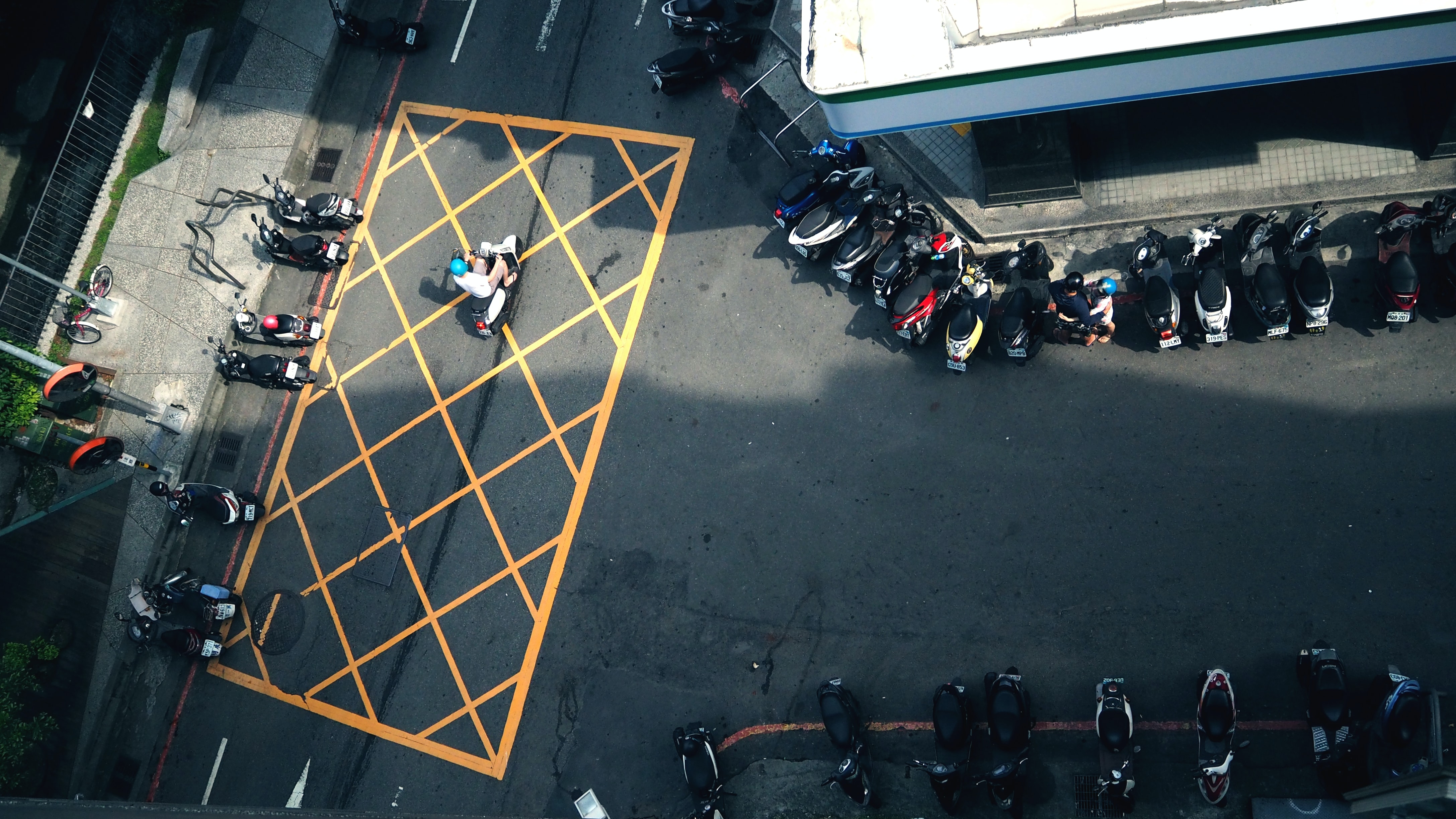 Drone view of street with buildings, sidewalks, and rows of mopeds and scooters in urban area