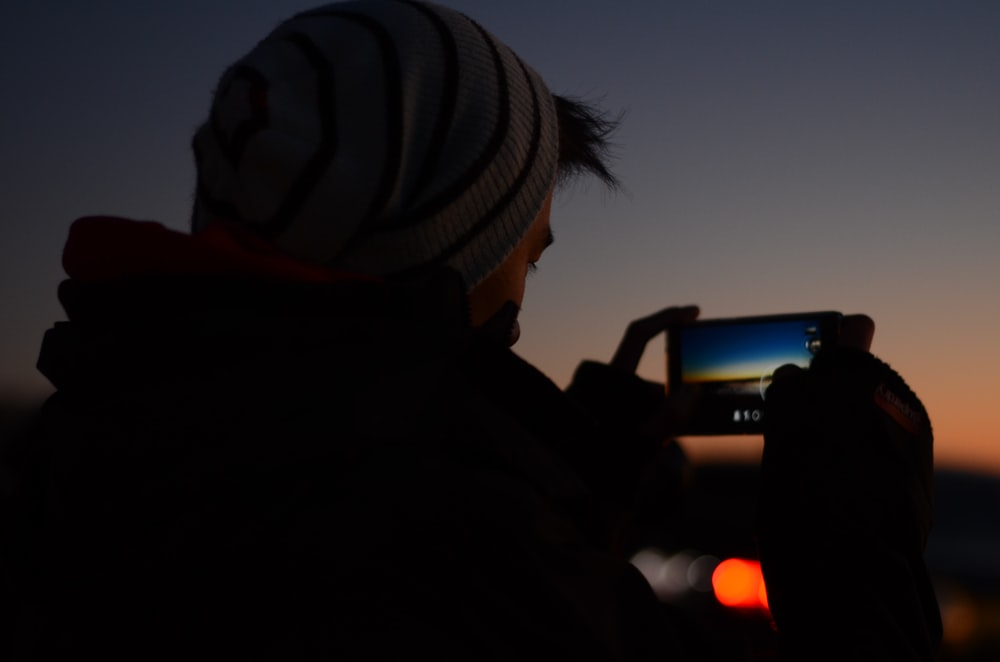 man holding phone to take a picture