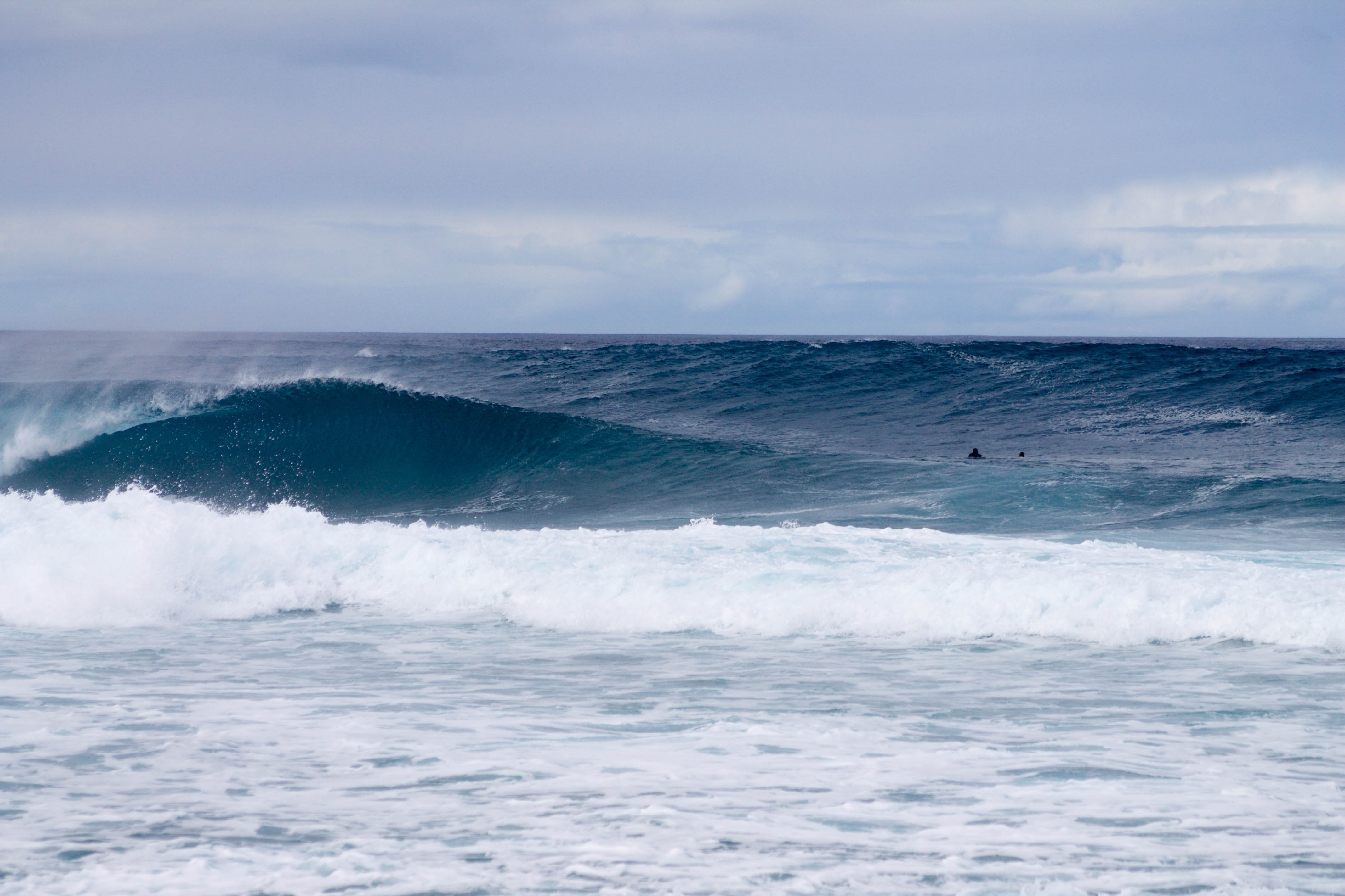 A large wave makes its way to the beach's shore.