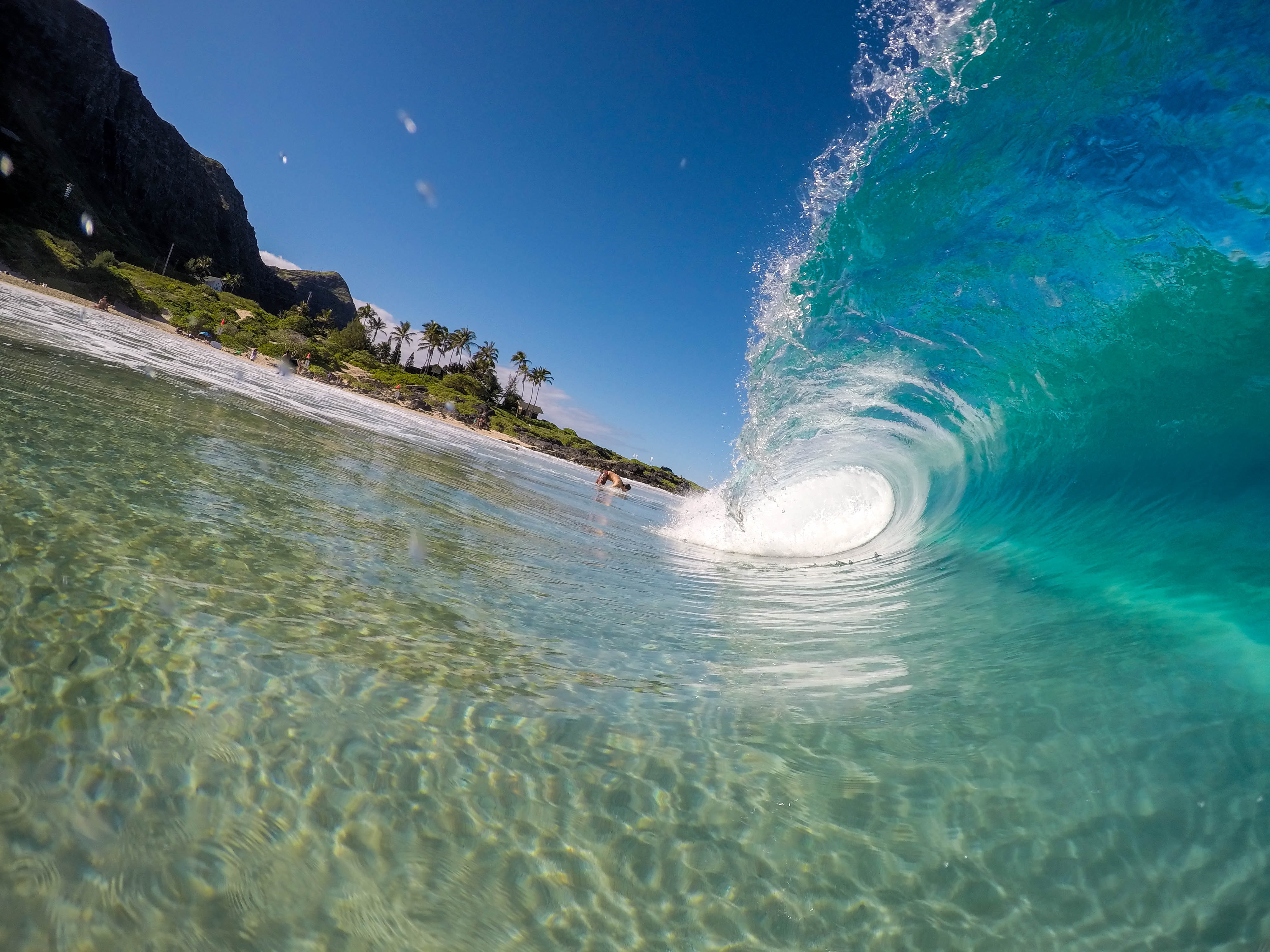 A transparent wave coming in near the shore.