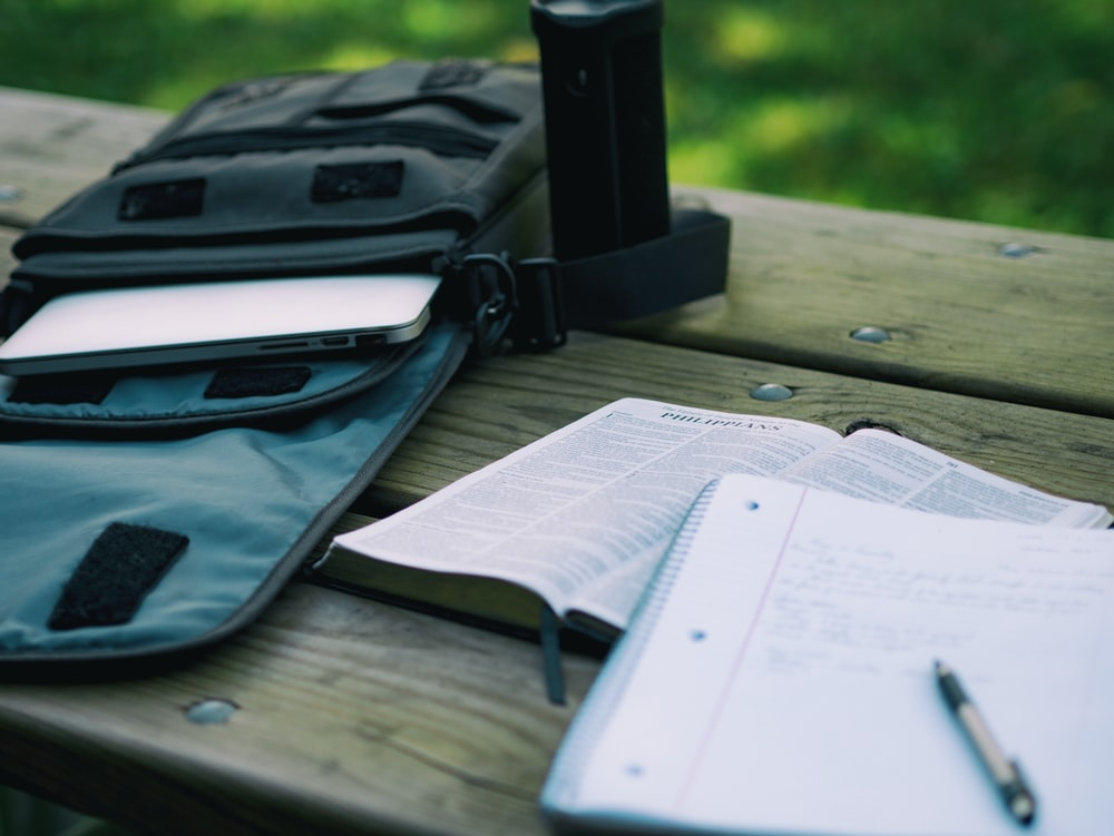 A notebook and a Bible on a bench next to a bag with a laptop