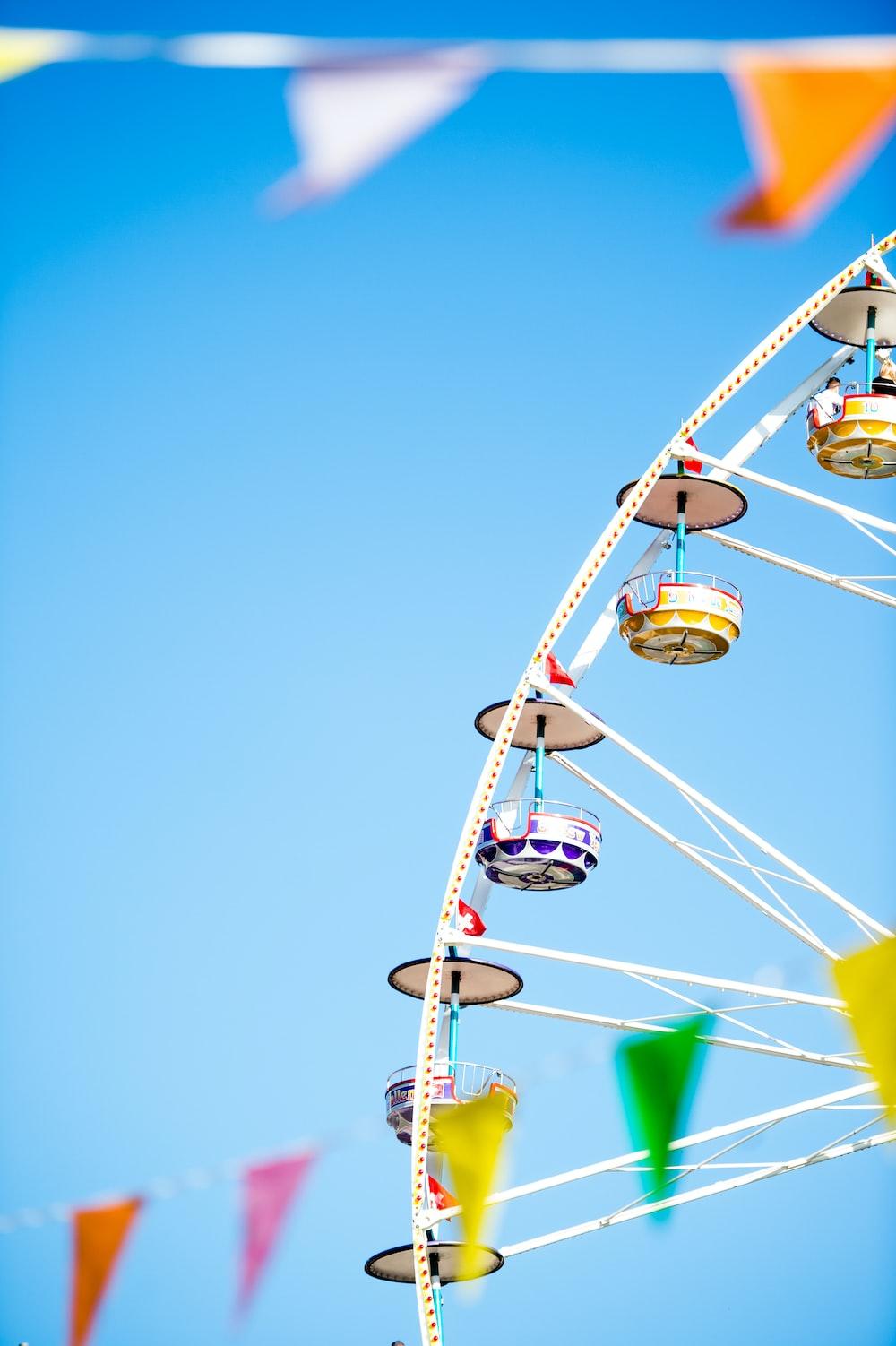 white and yellow Ferris wheel under blue skies photo