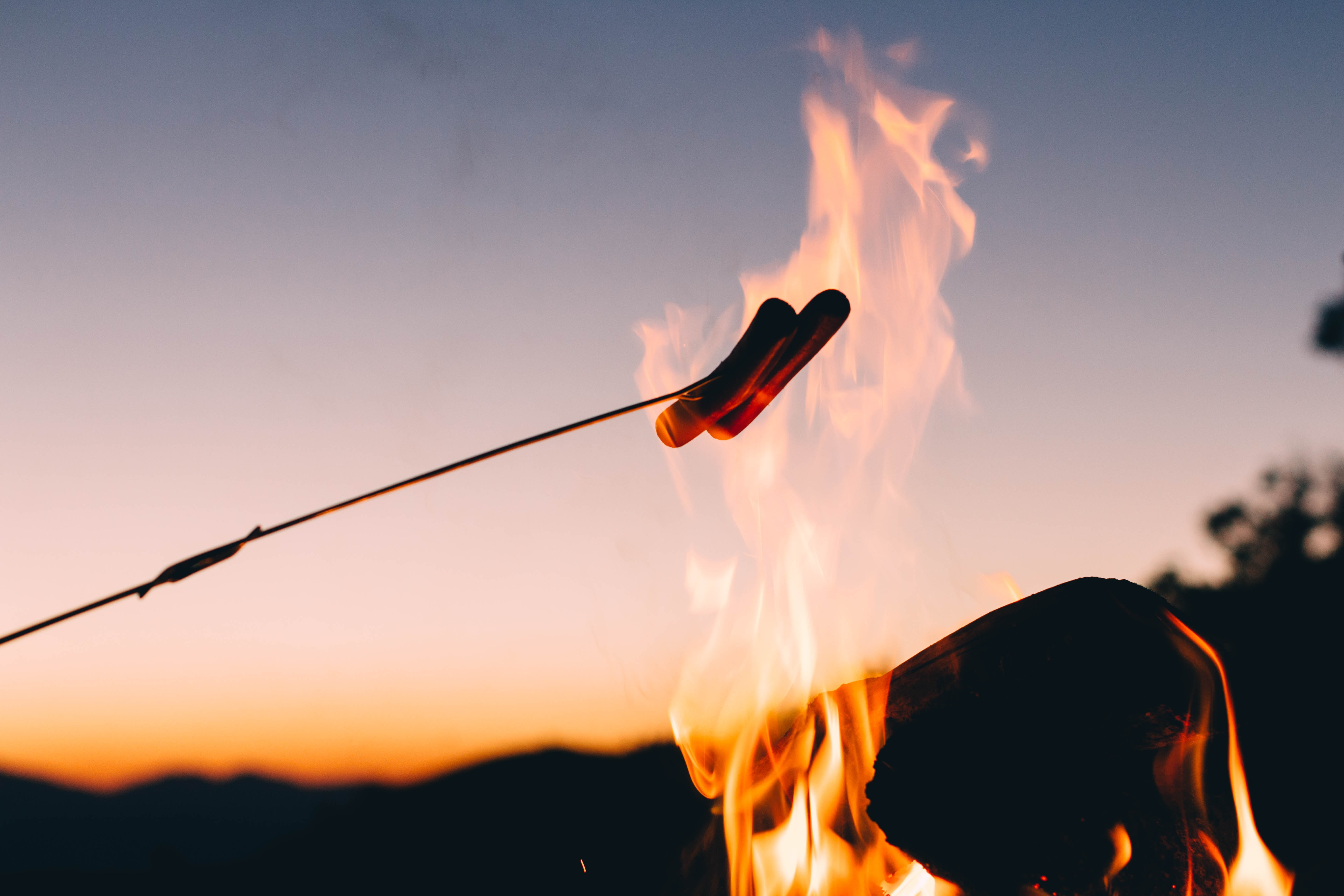 Roasting hotdogs over an open campfire at night