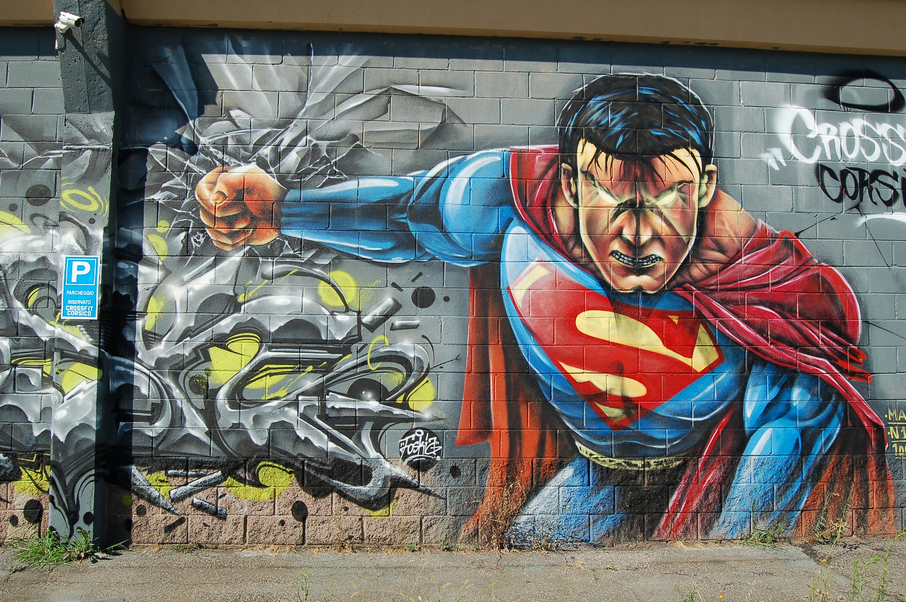 An intense graffiti painting of Superman on a building wall.