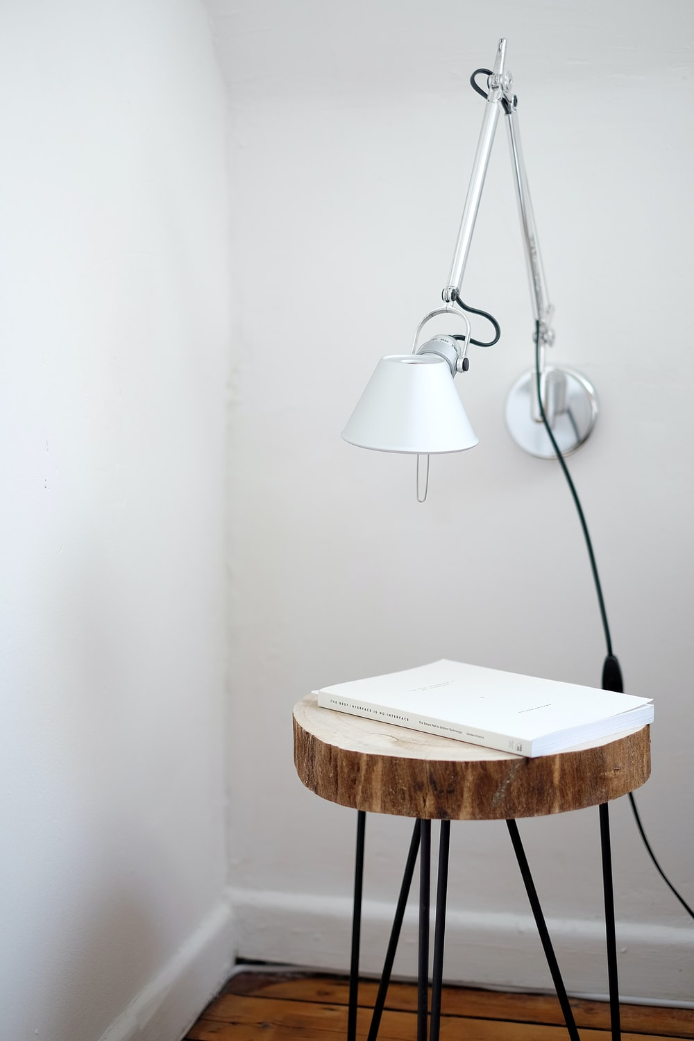 gray desk lamp mount on white wall under brown stool with white book on top near wall corner