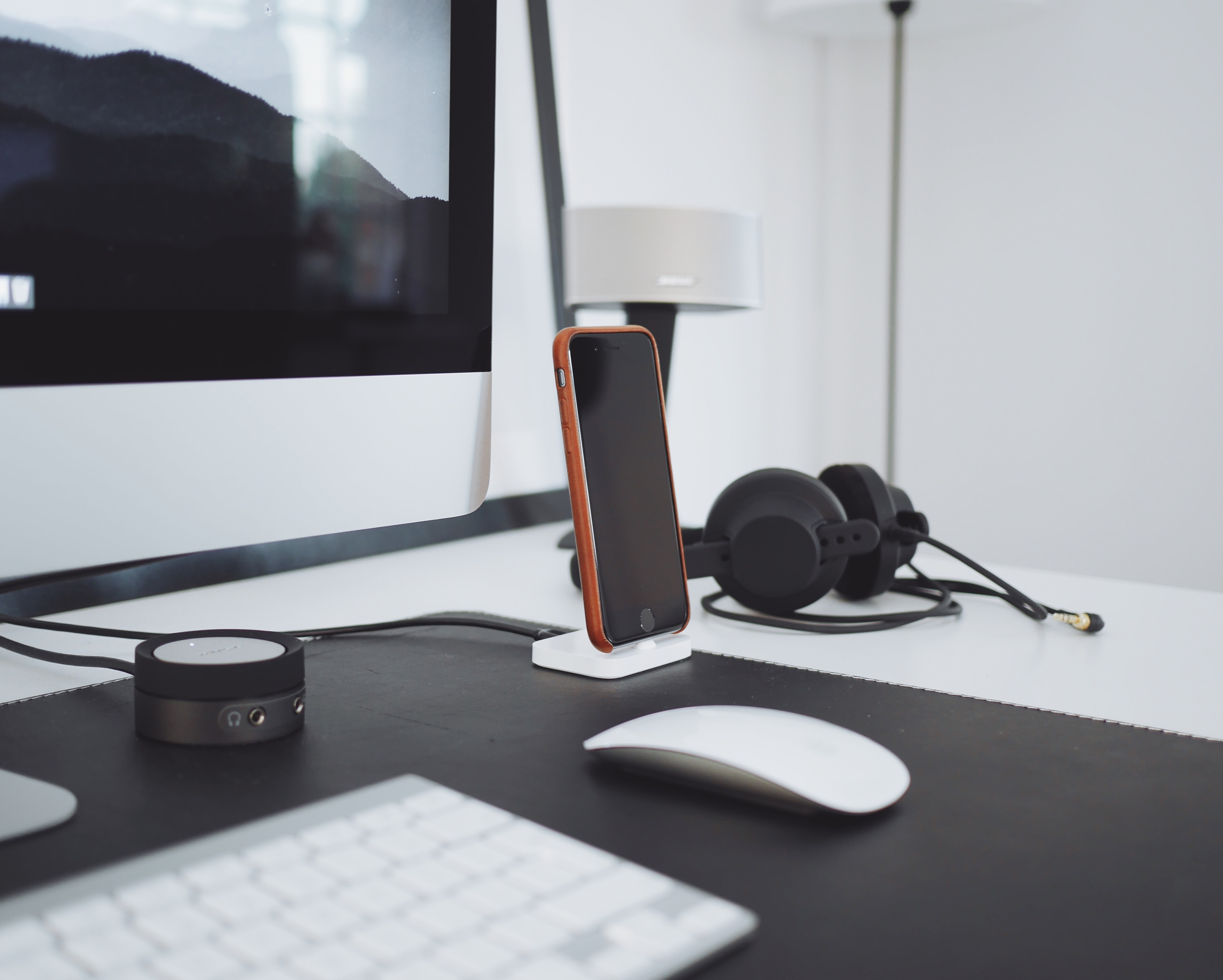An iPhone near a pair of headphones and a small speaker on a computer desk