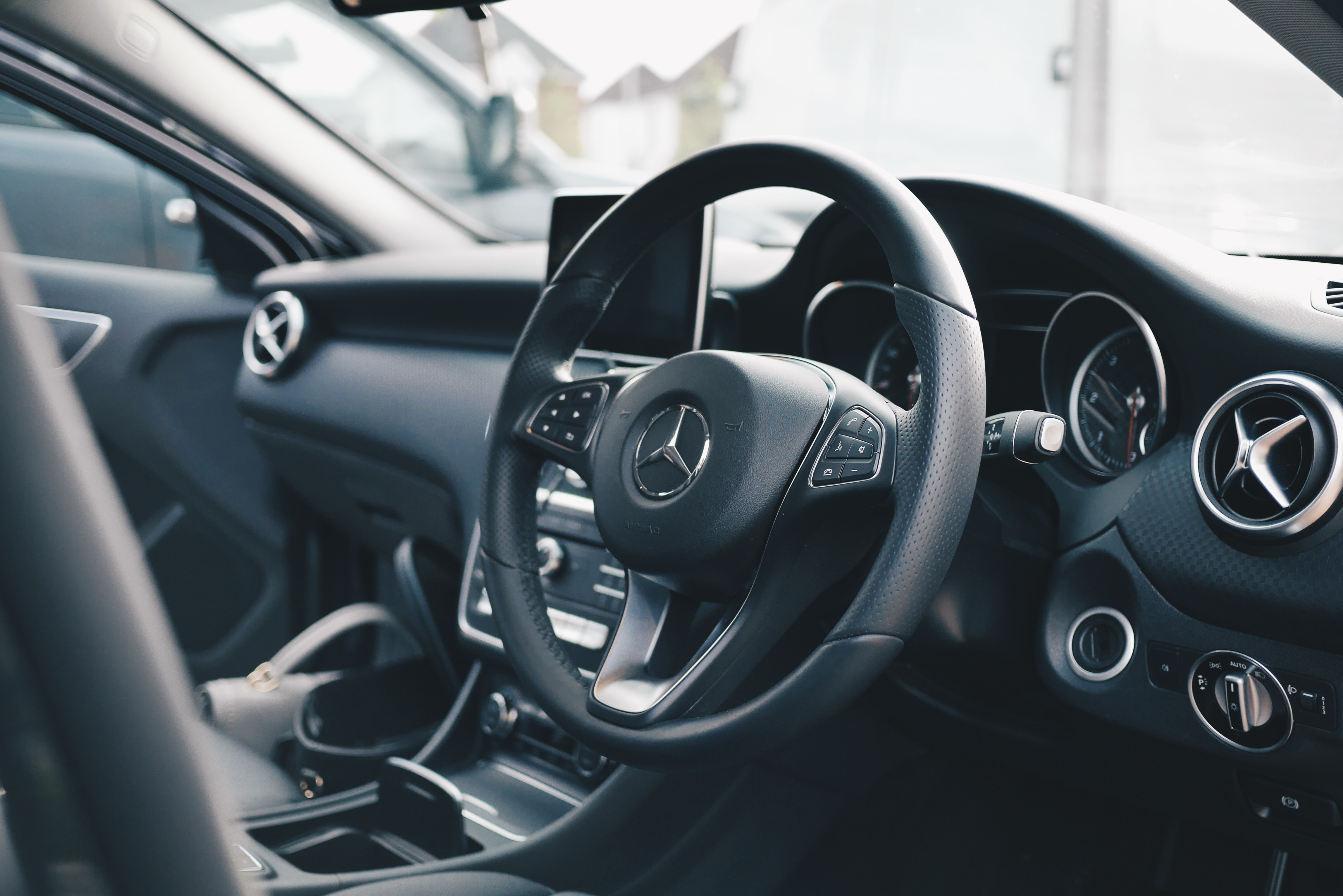 Interior of a Mercedes Benz car centered on the steering wheel