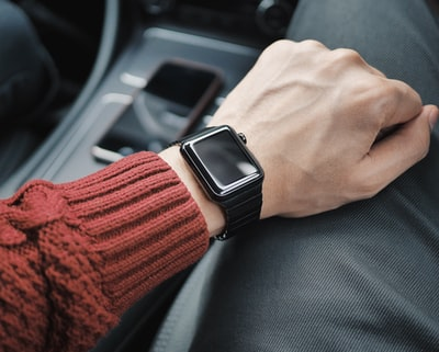 person wearing black case apple watch with white sport band apple watch zoom background