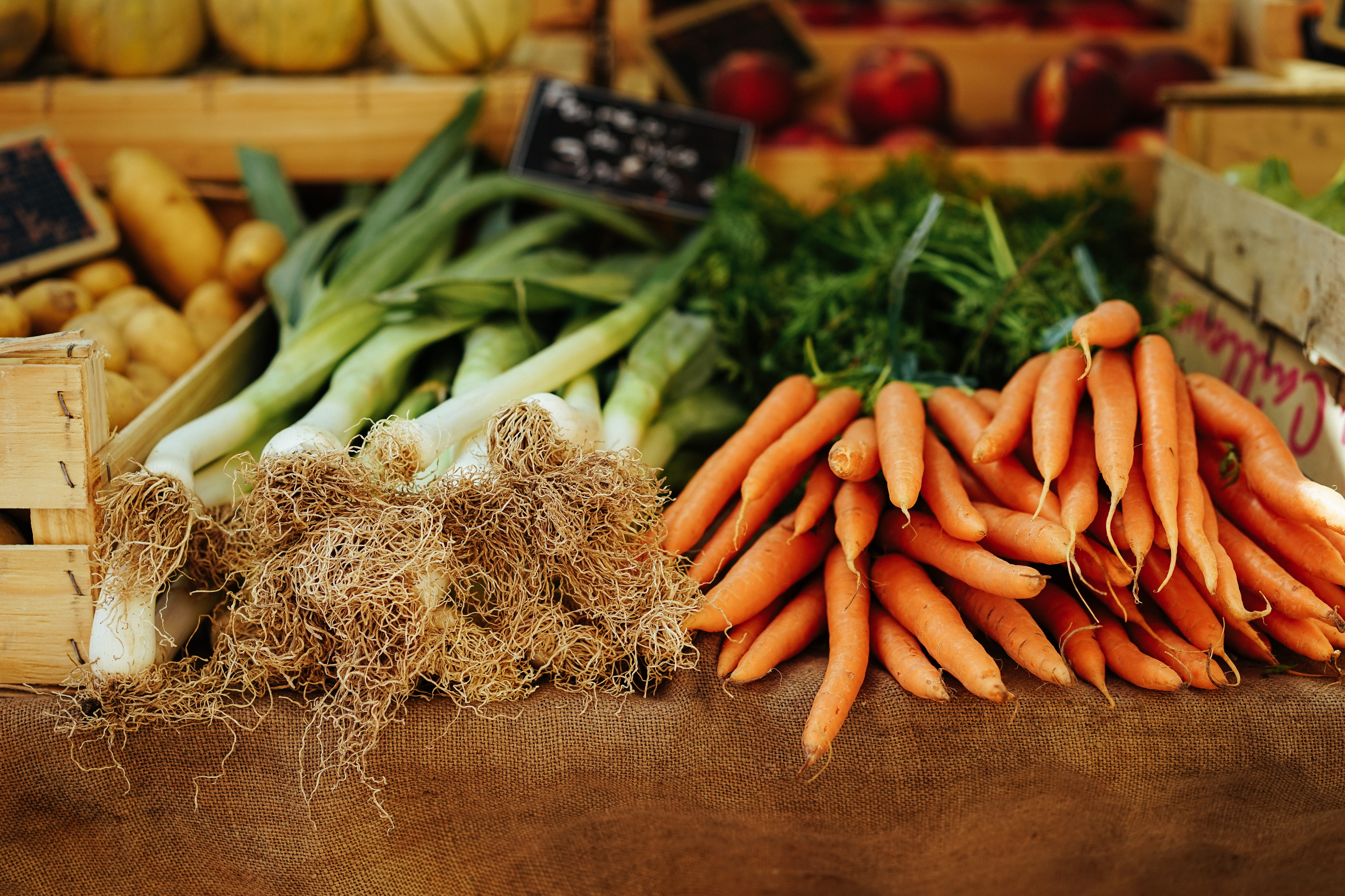 A table full of vegetables including celery and carrots at Marché aux Fleurs