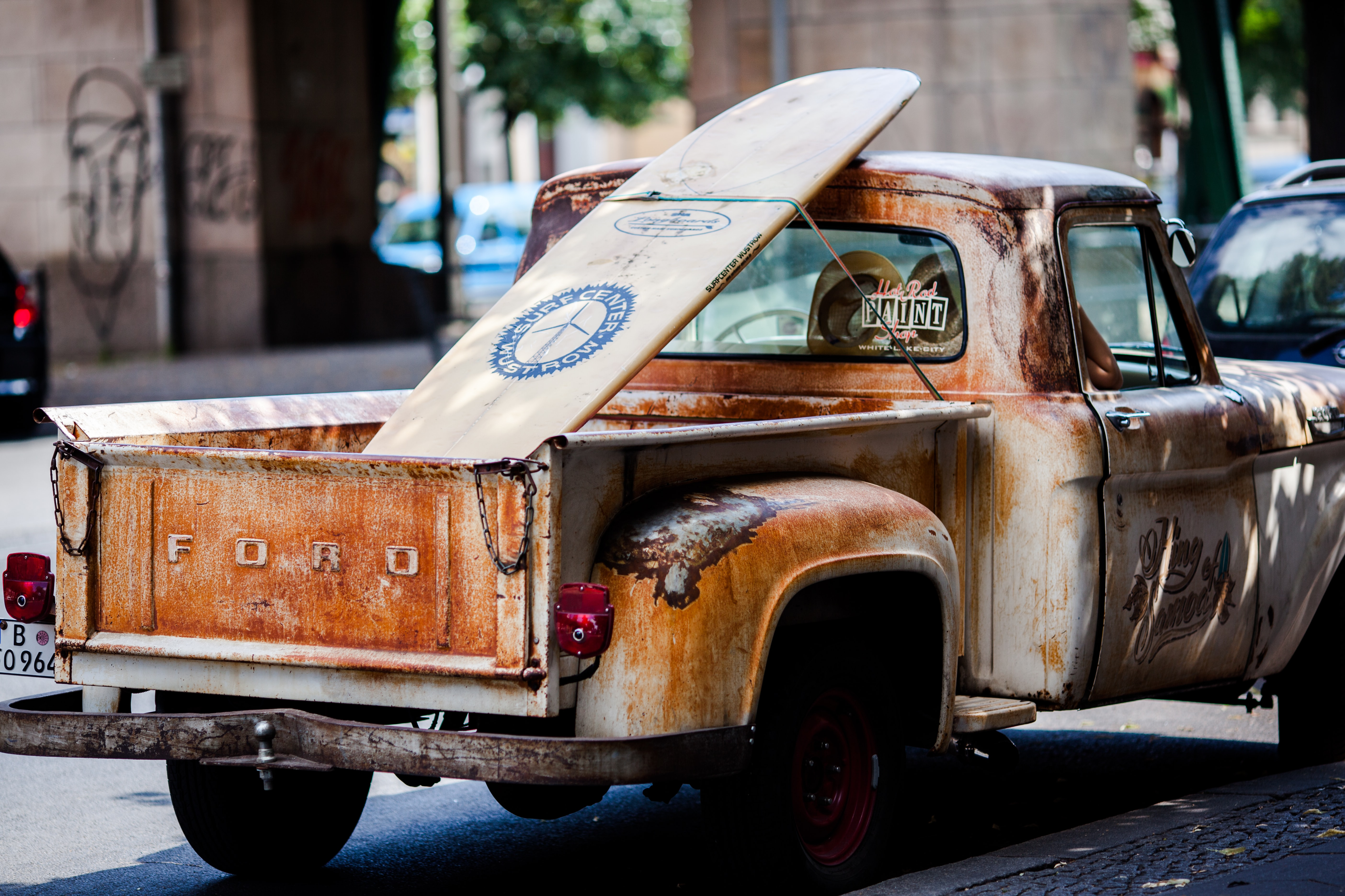A rusty pick-up truck with a white surfboard in the cargo area