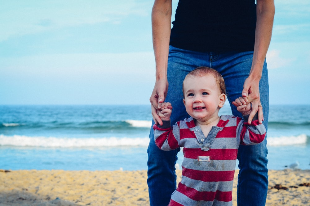 man assisting baby to walk on beach