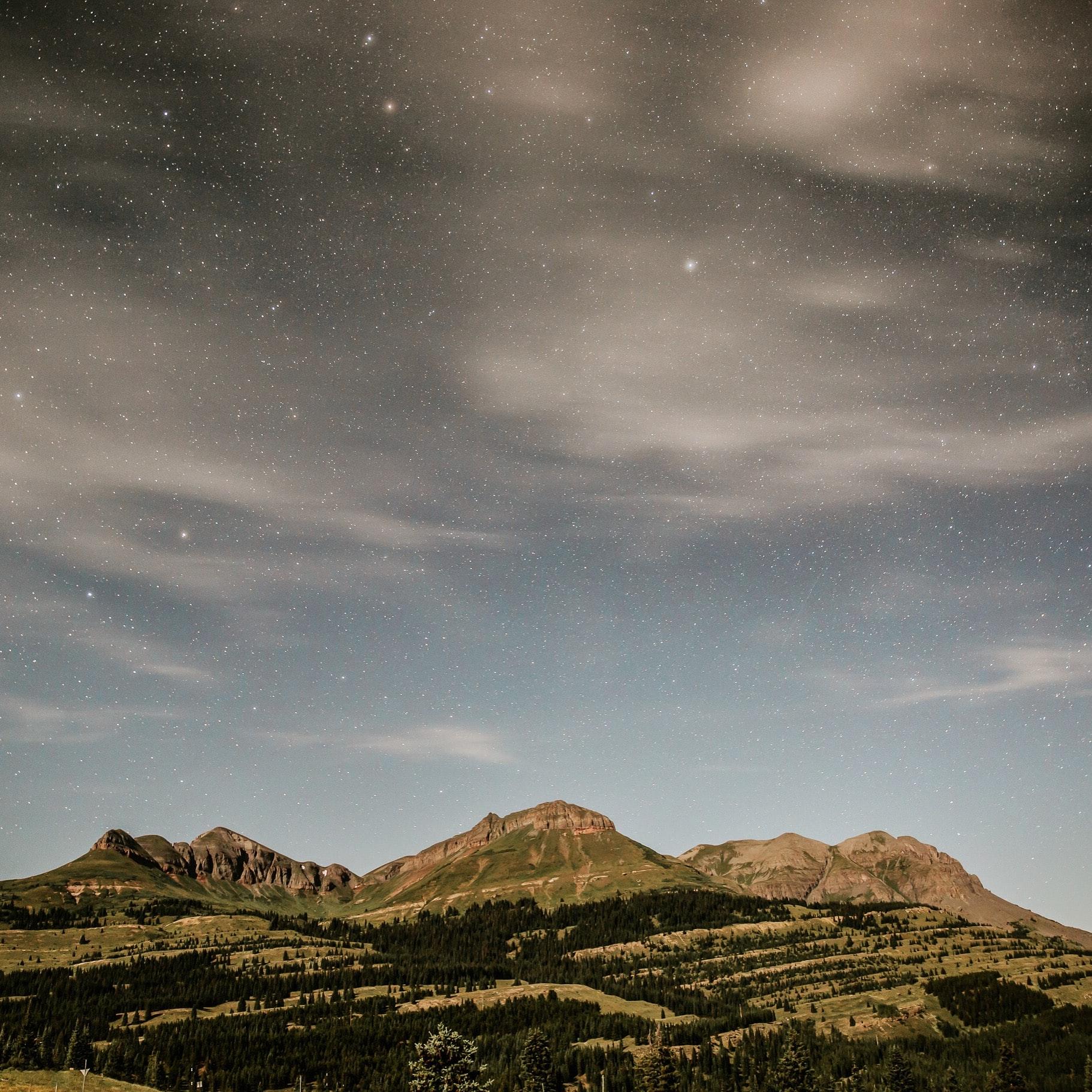 Wooded plains and low mountains below a starry sky in the evening