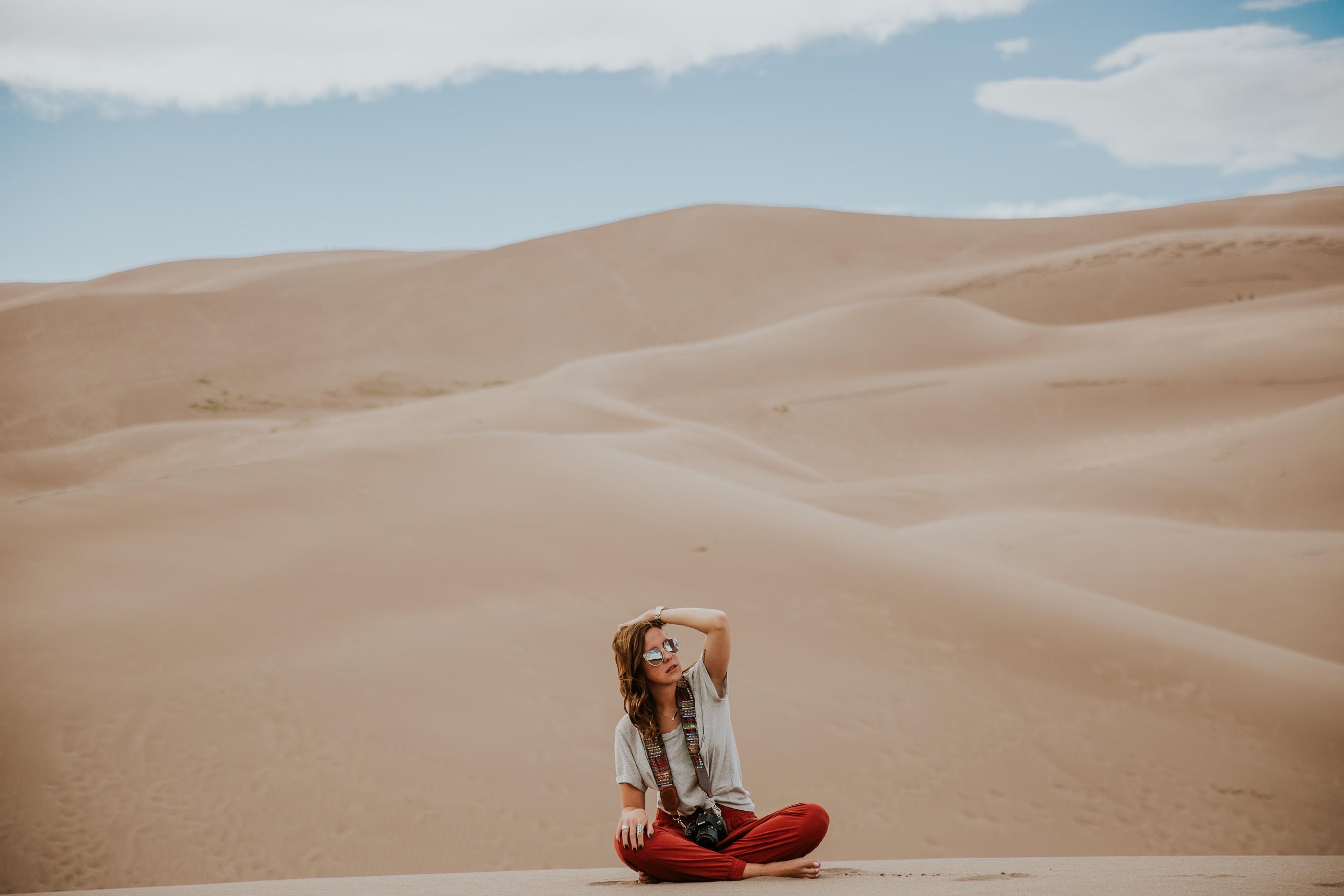 minimalist photography of woman sitting on desert ground