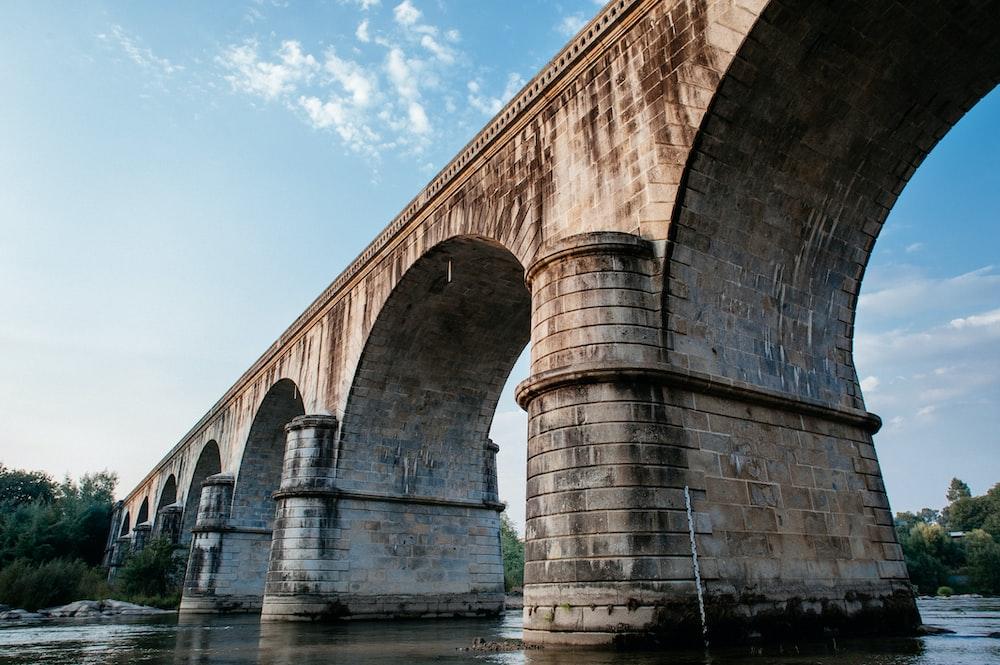 brown concrete bridge over river under blue sky during daytime
