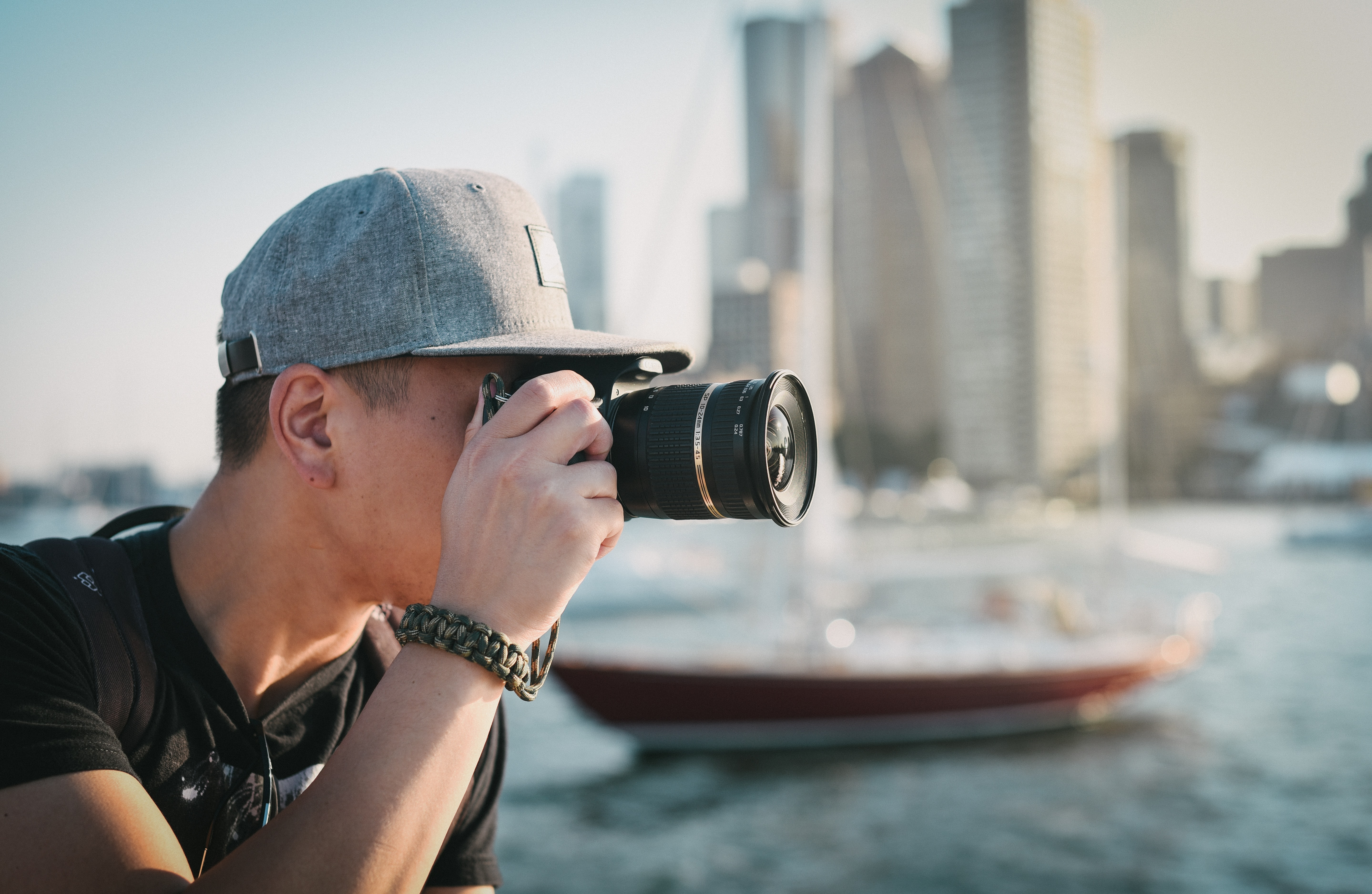A man wearing a cap and holding a camera with buildings and a boat beside him