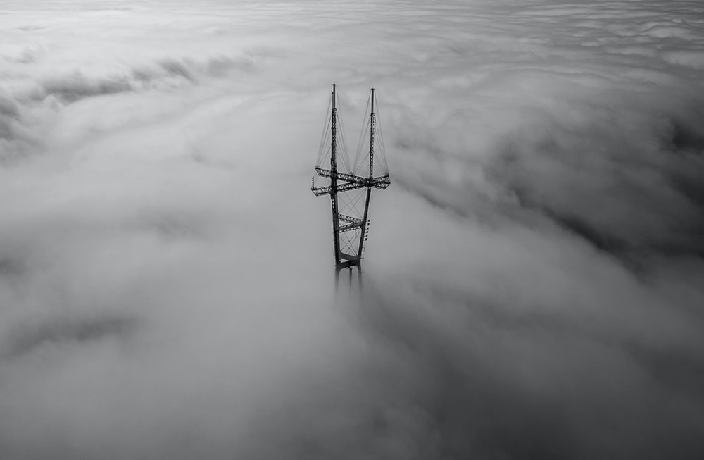 grayscale photo of tower surrounded by clouds