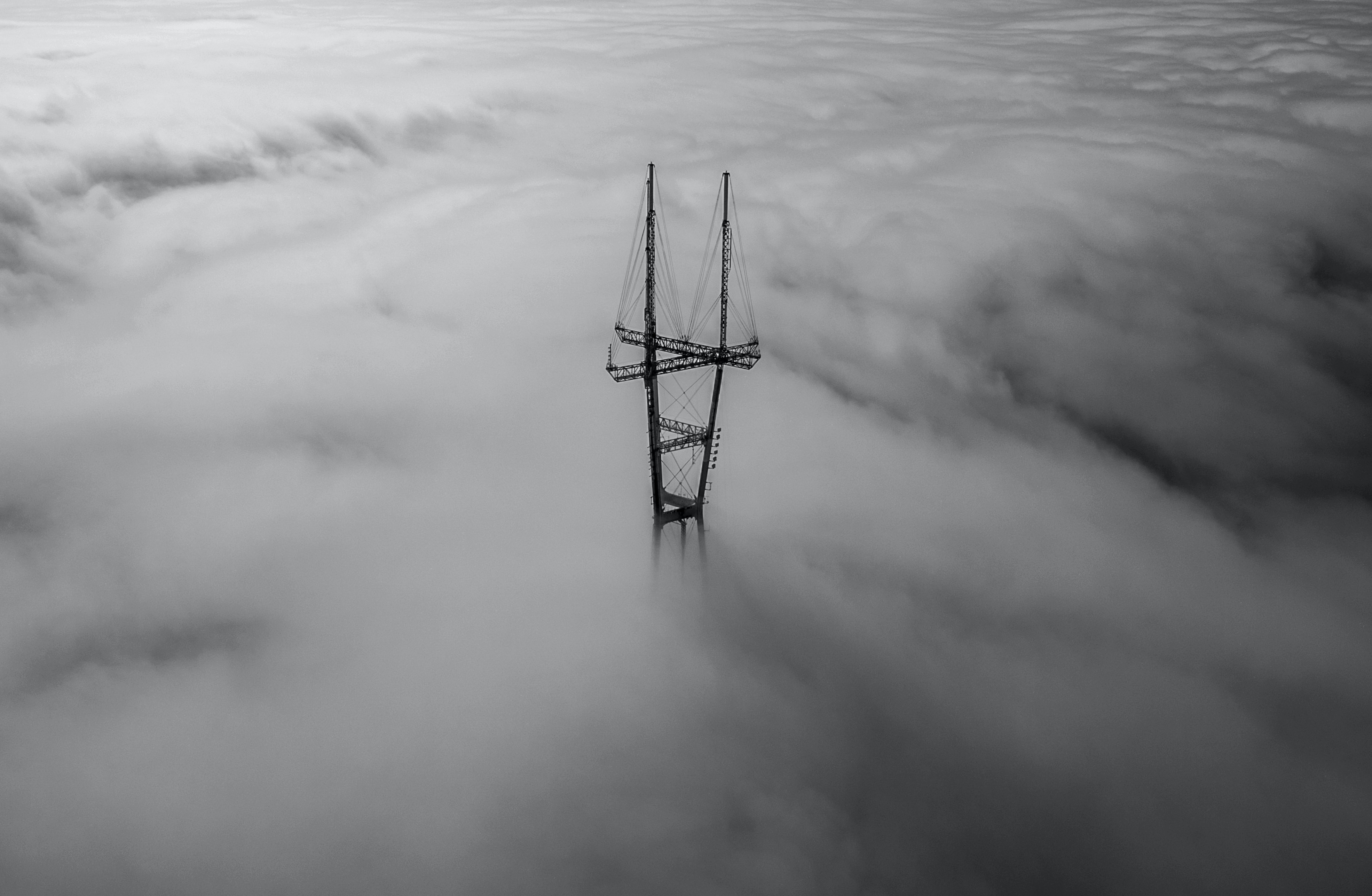 Black and white drone shot of Sutro Tower emerging from thick clouds