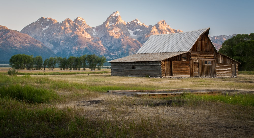 gray wooden barn near the mountain range under the gray skies