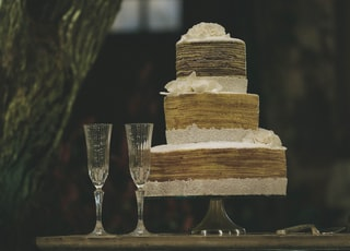 two clear wine glasses beside 3-layer towel cake