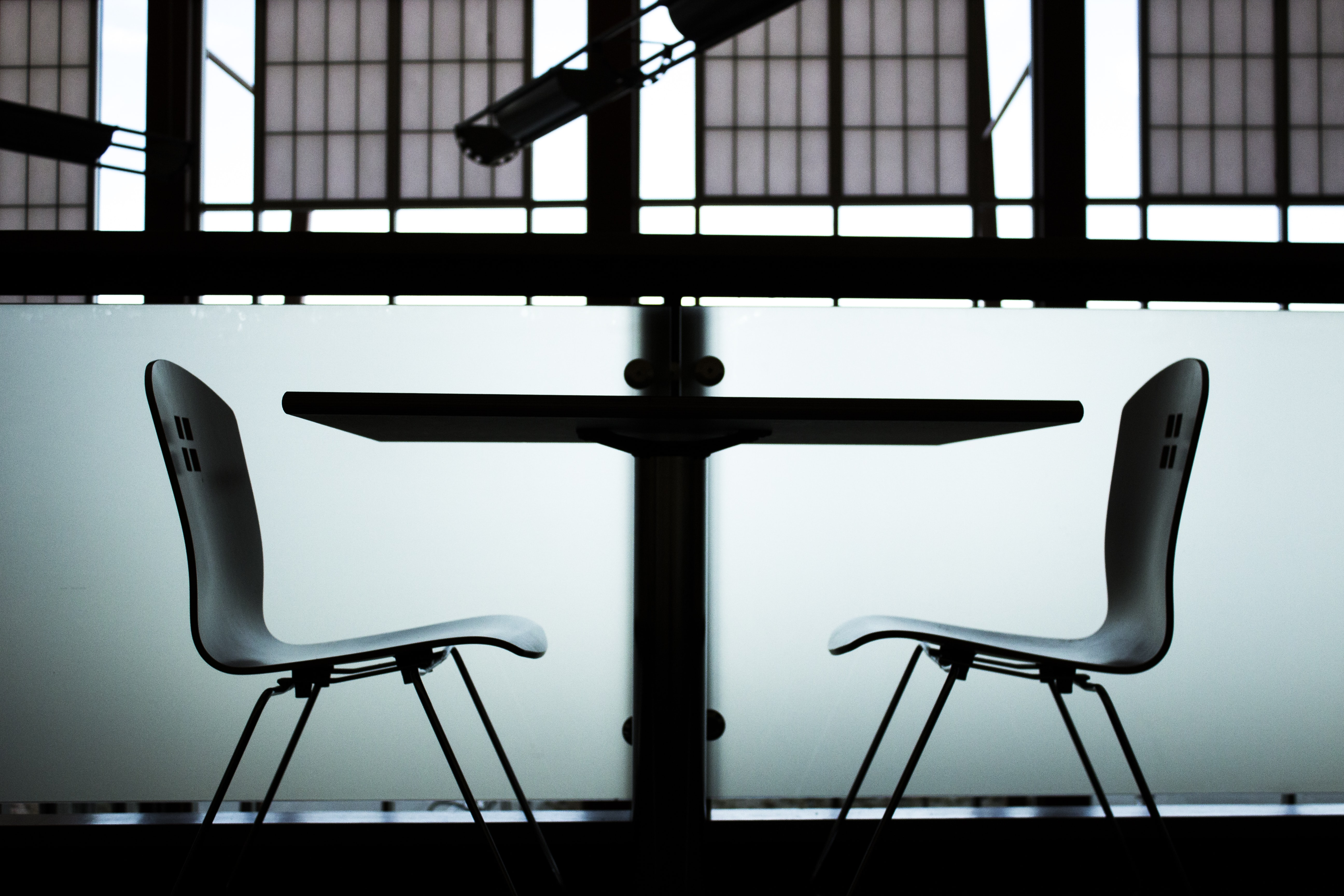 A gloomy side shot of two chairs on two sides of a table