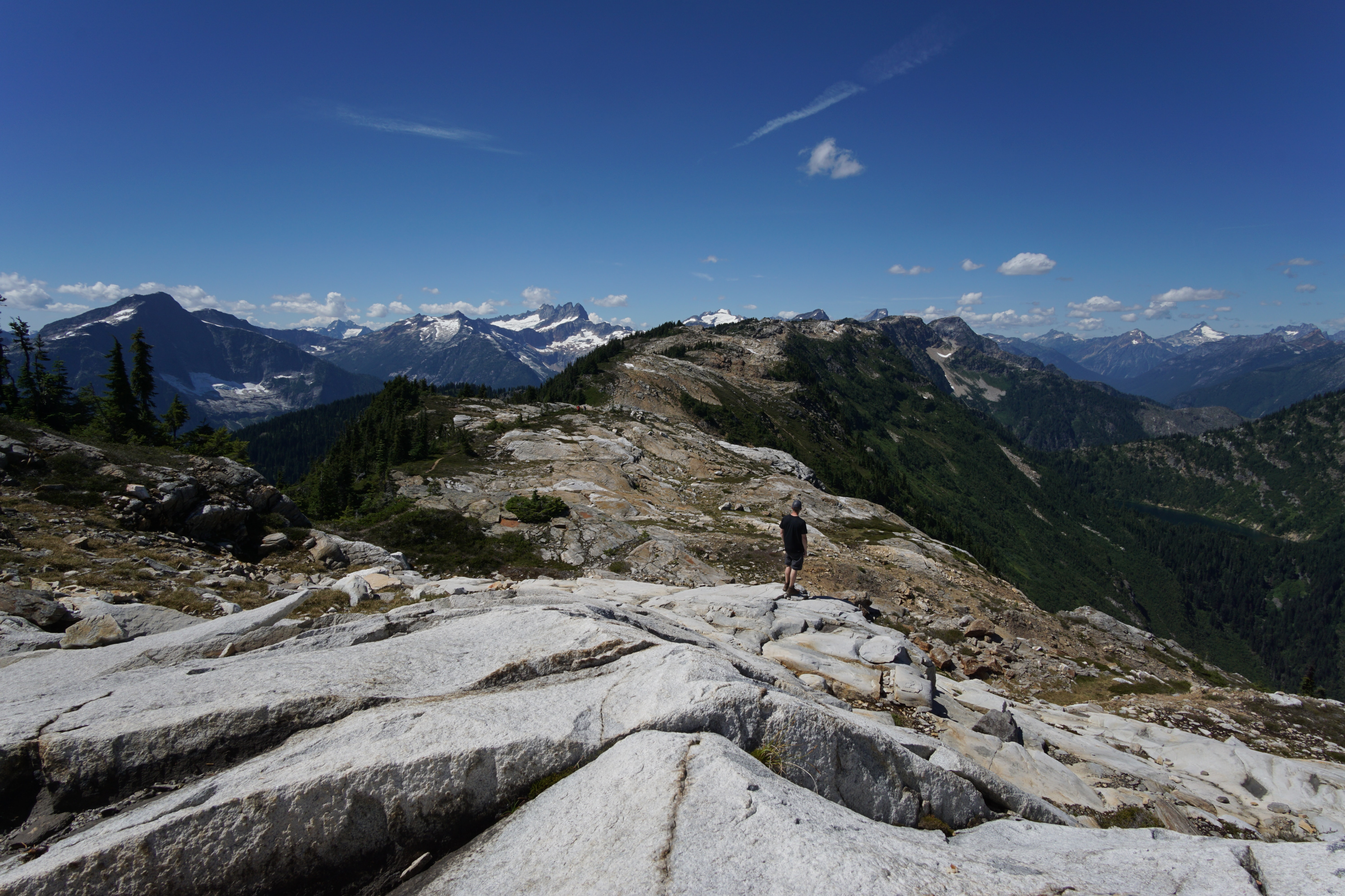 person standing on rock facing mountains during daytime