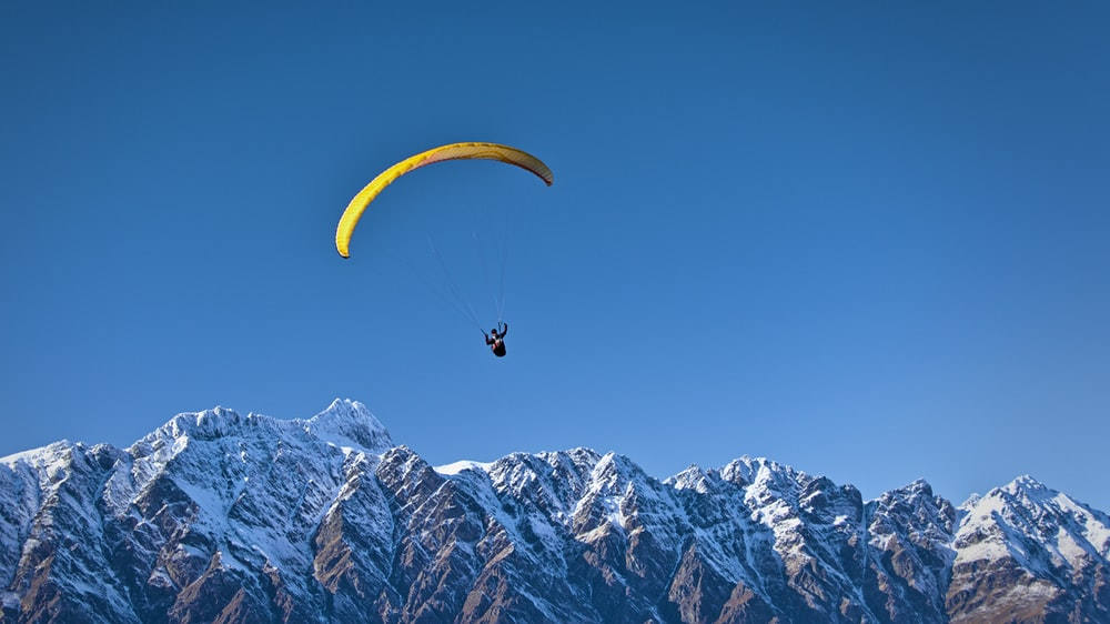 man in parachute near mountain