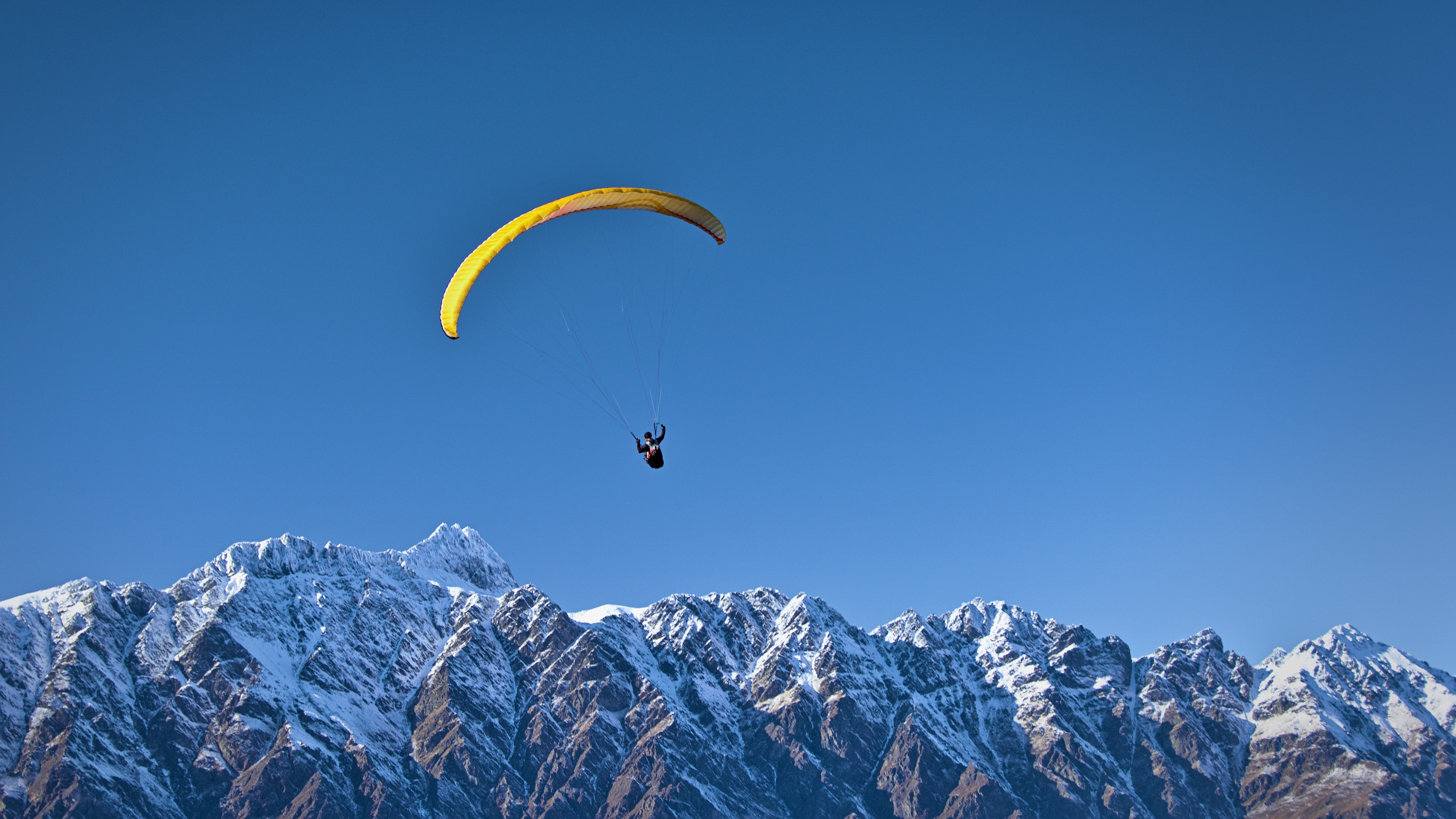A paraglider soaring over snowy mountains