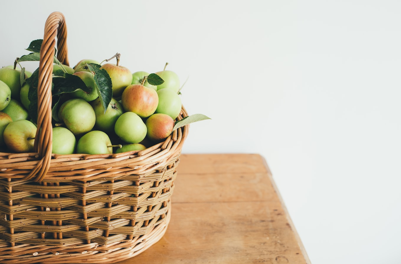 A basket containing green and red apples