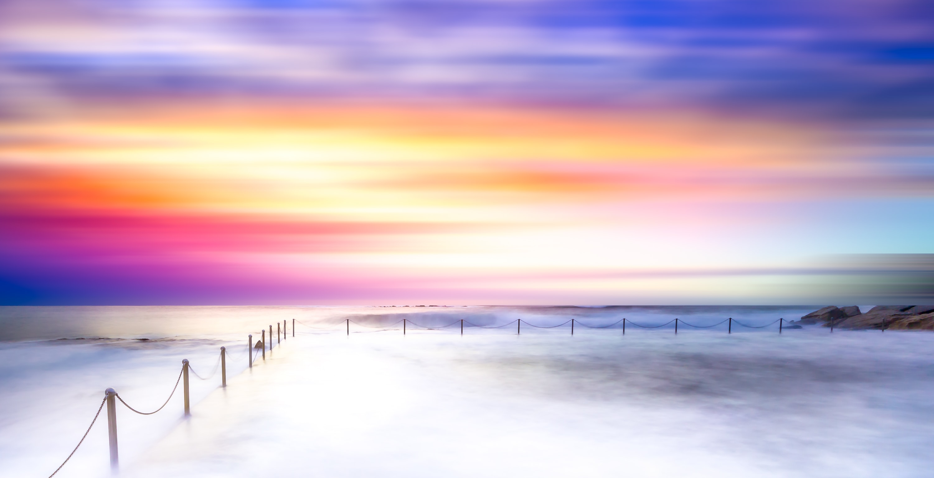 Illuminated sky with rainbow colors over the sea in Sydney with fences in the foreground.