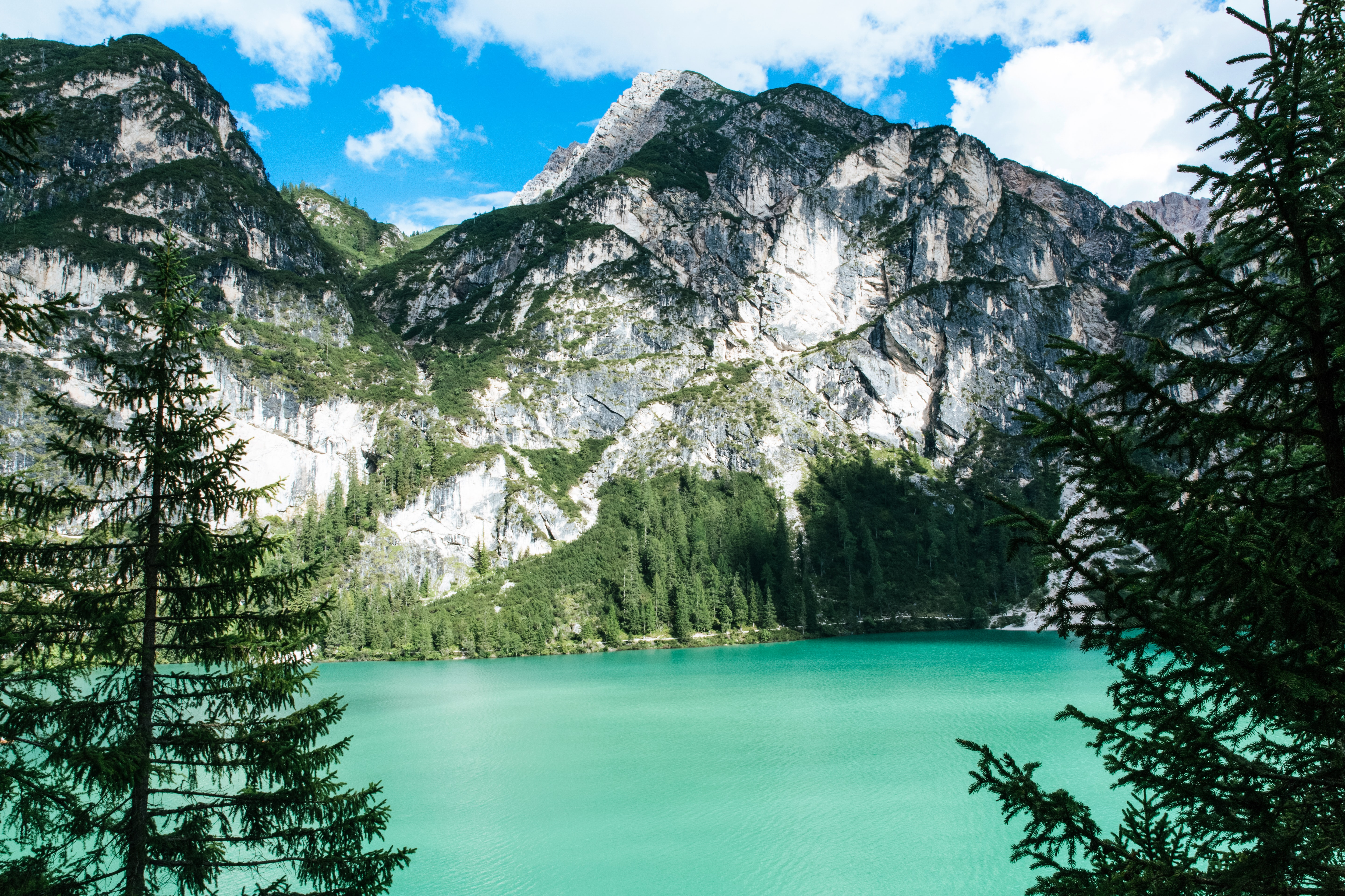 A picturesque landscape with a turquoise lake at the foot of a rugged mountain