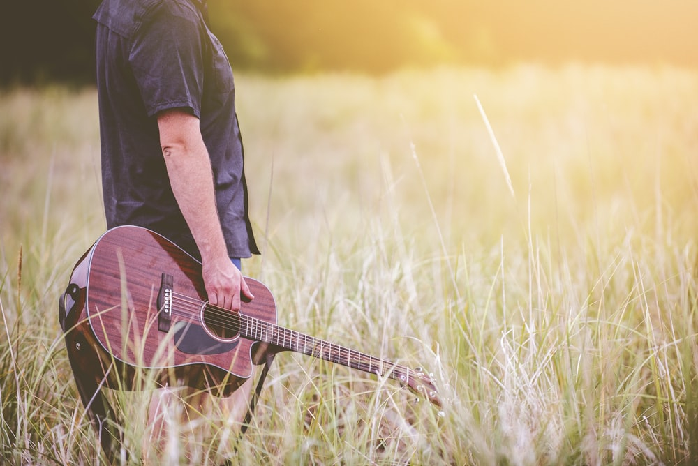 man carrying brown cutaway acoustic guitar standing on green grass field