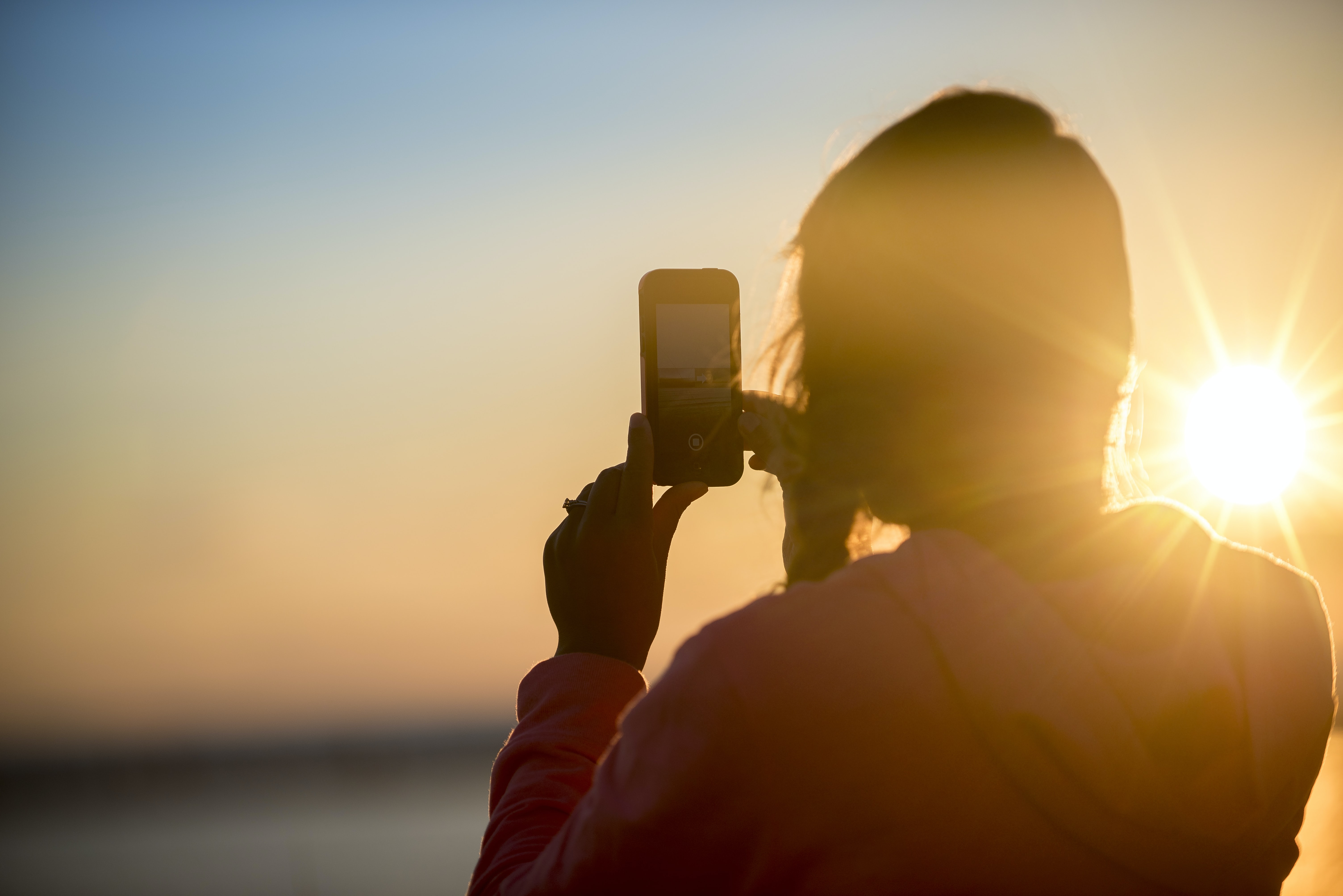 A woman on the beach taking a photo on her smartphone during golden hour