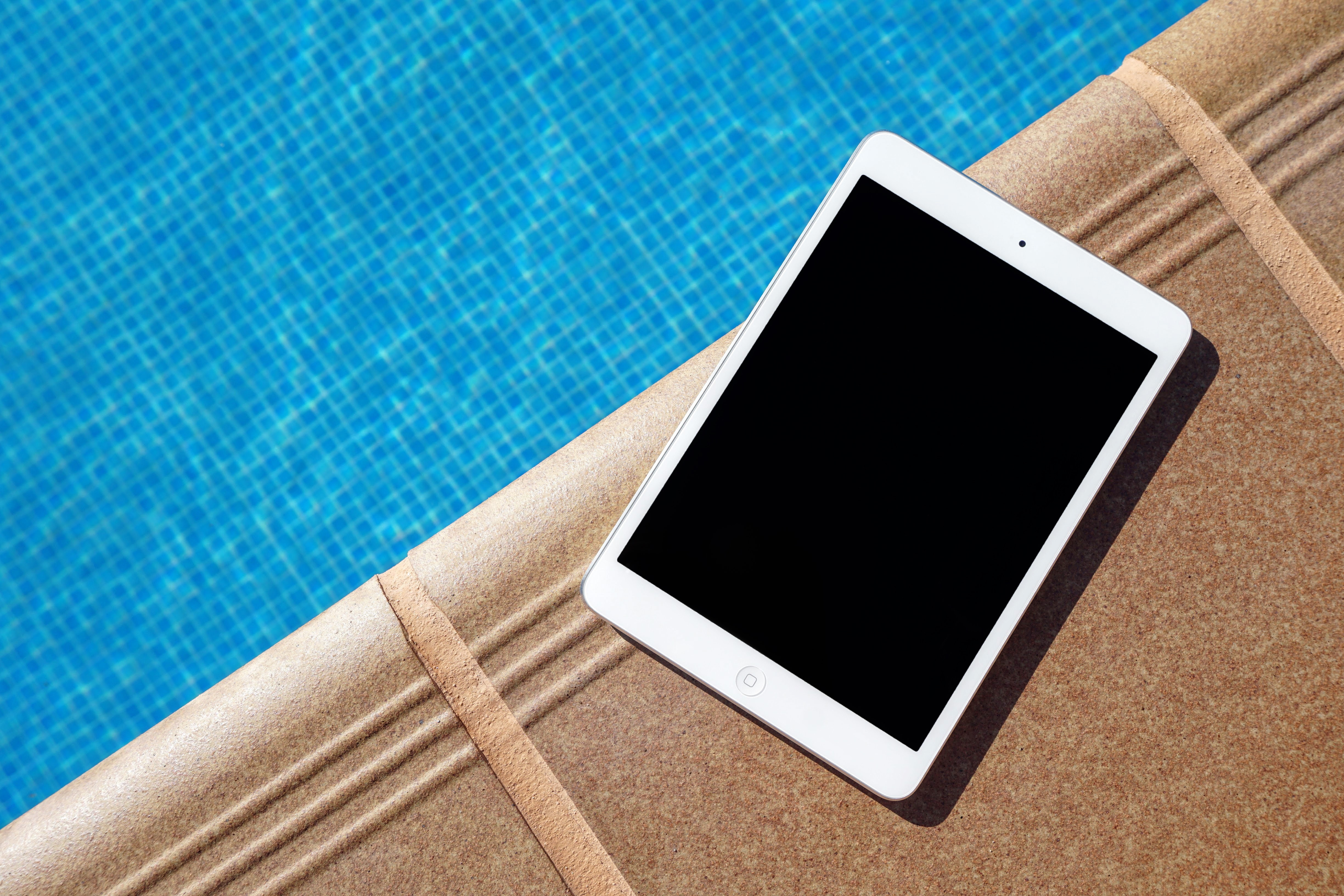 An iPad on the edge of a swimming pool