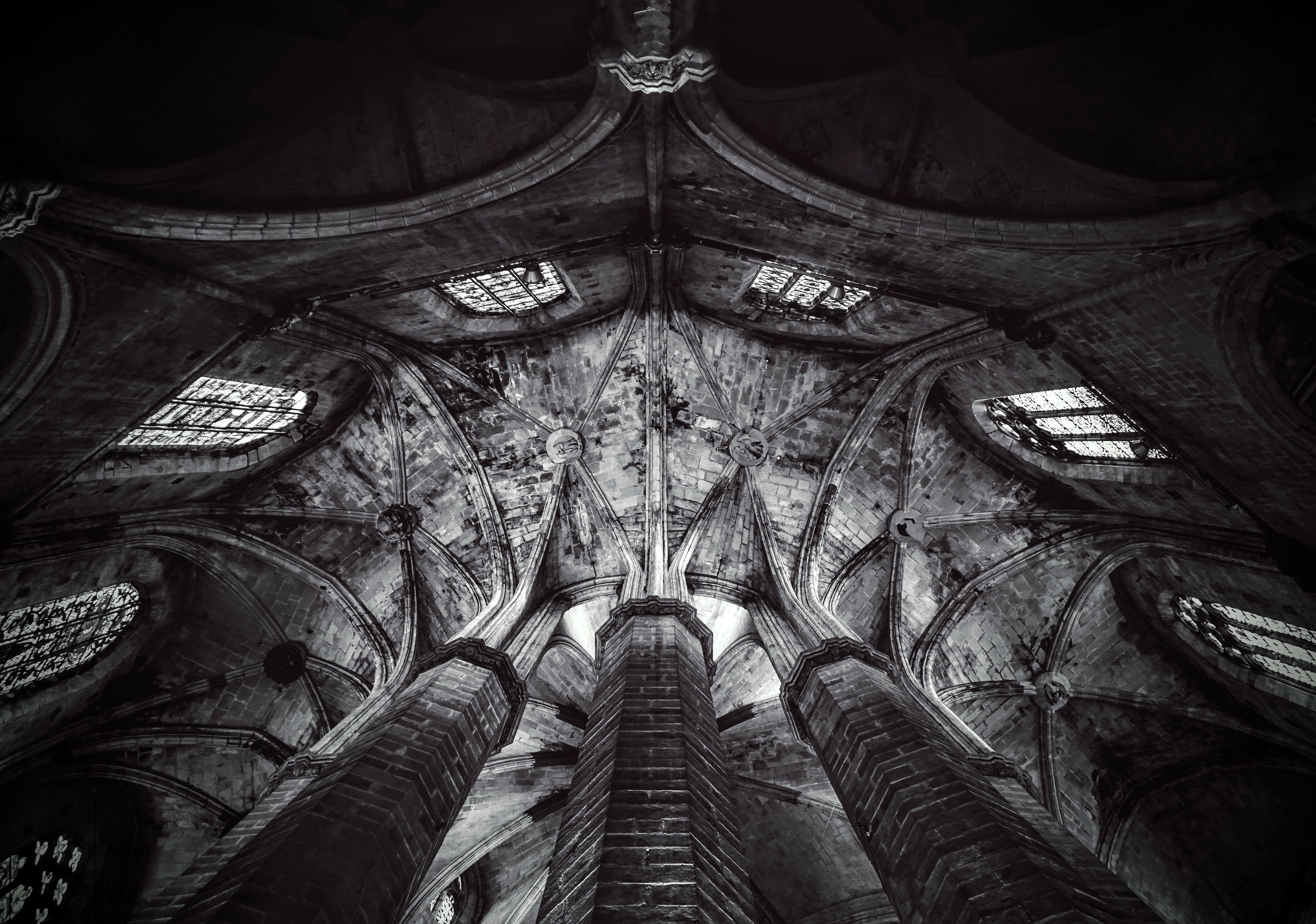 Black and white shot of gothic ceiling, pillars and stained glass window in Barcelona