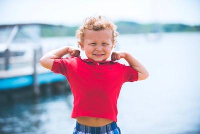 boy standing near dock kid teams background