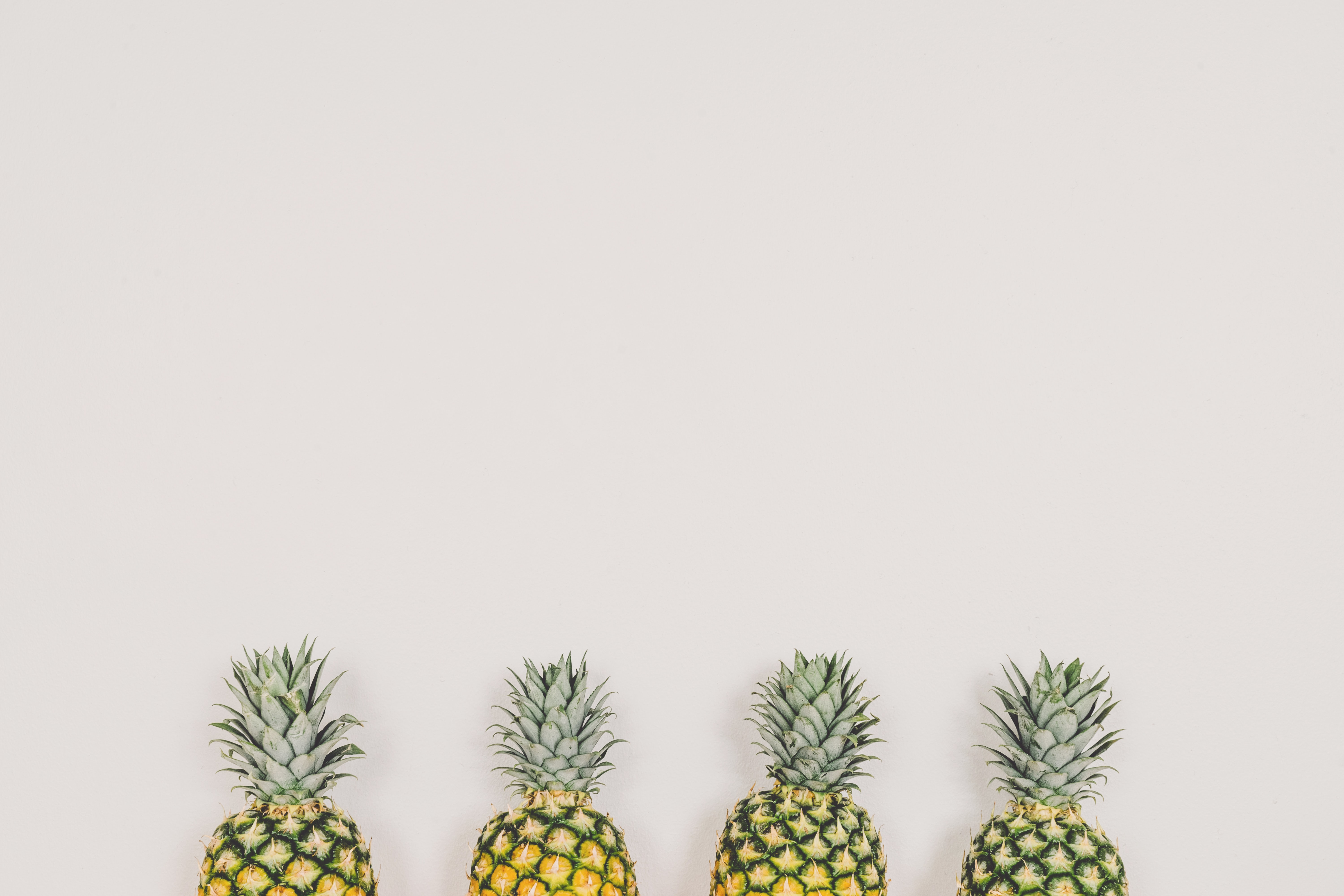 Four pineapples arranged in a row against a white wall