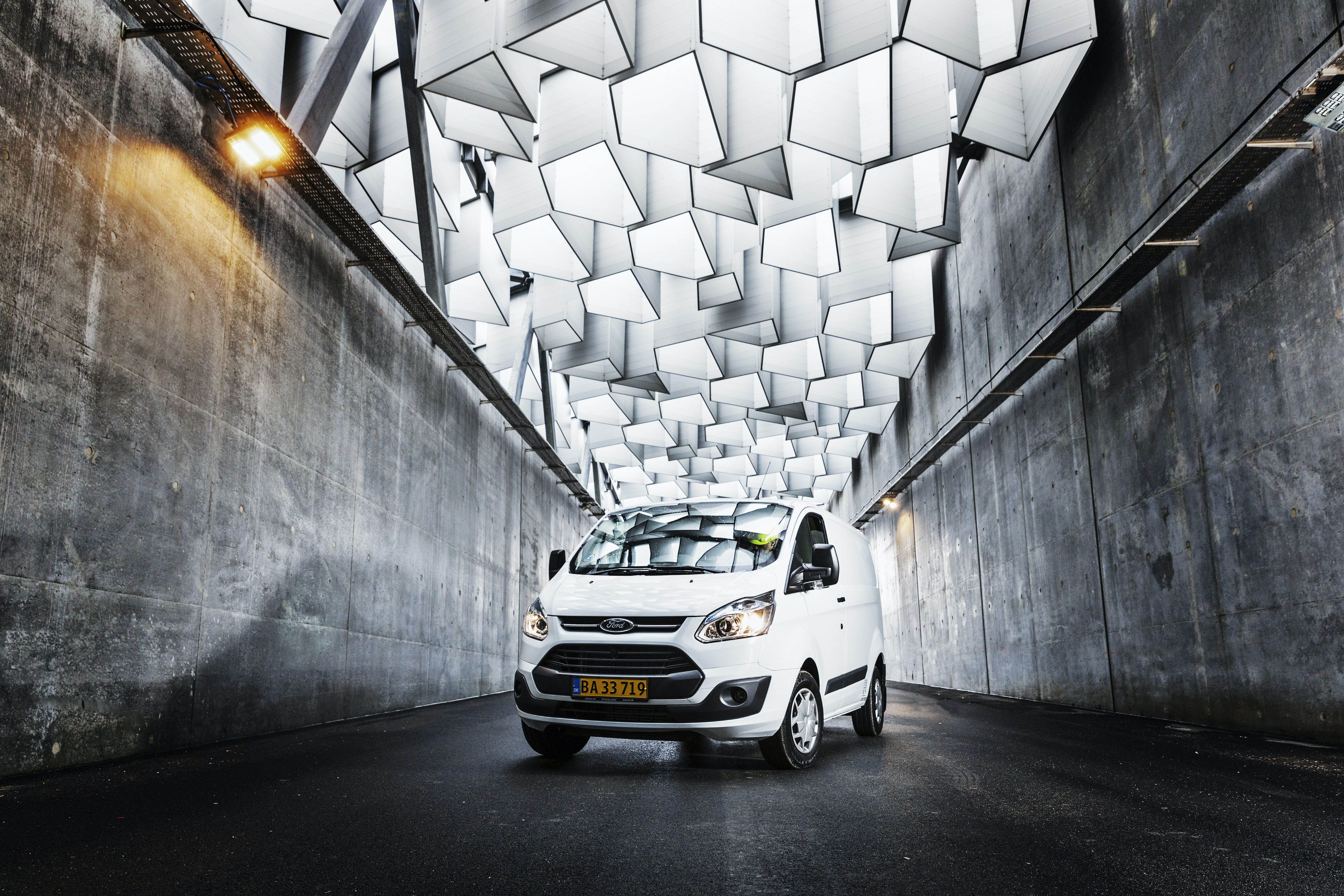 White Ford transportation van in an underground concrete and contemporary lit tunnel in Copenhagen