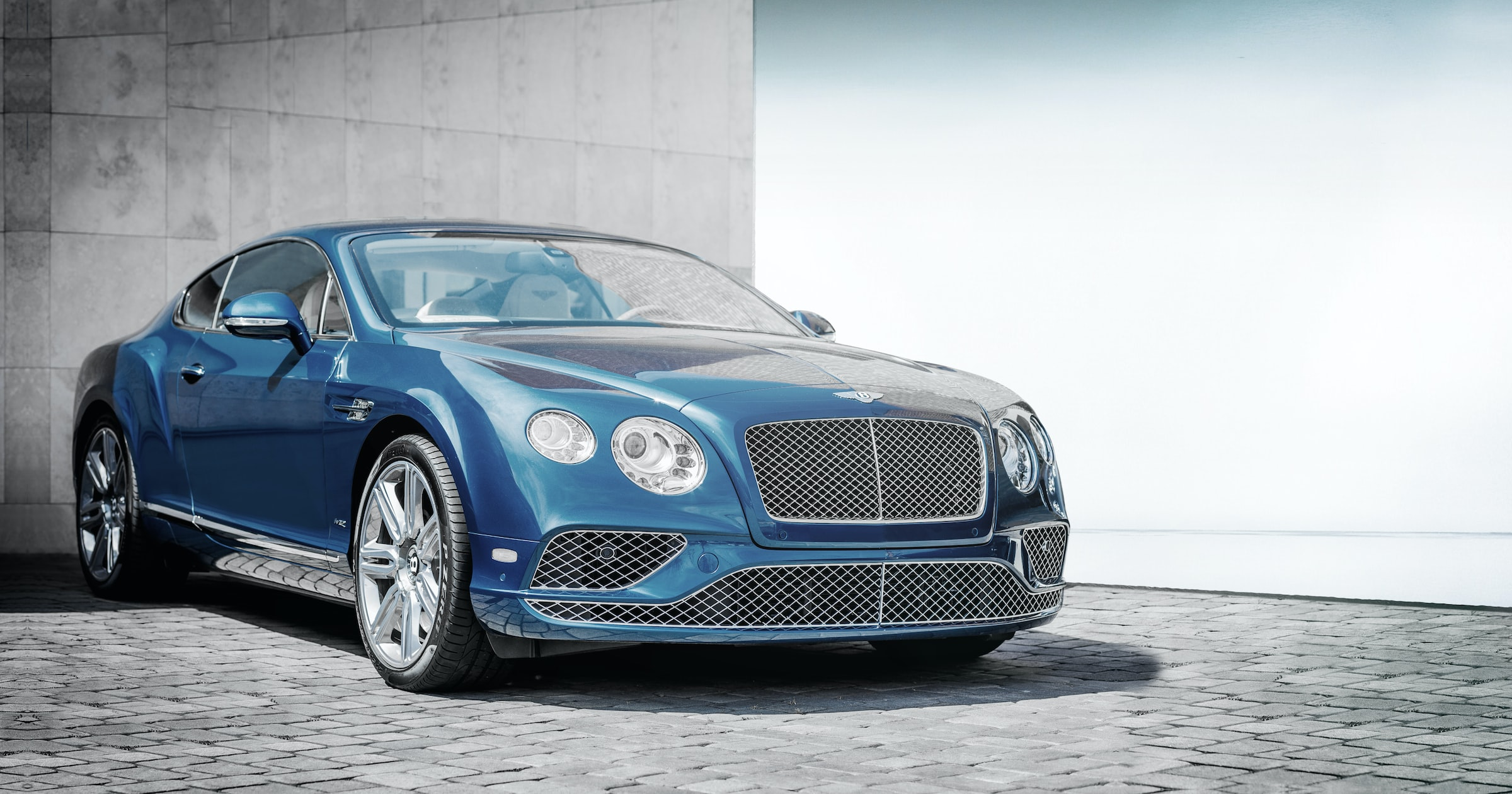 Luxury blue Bentley car parked on a gray street