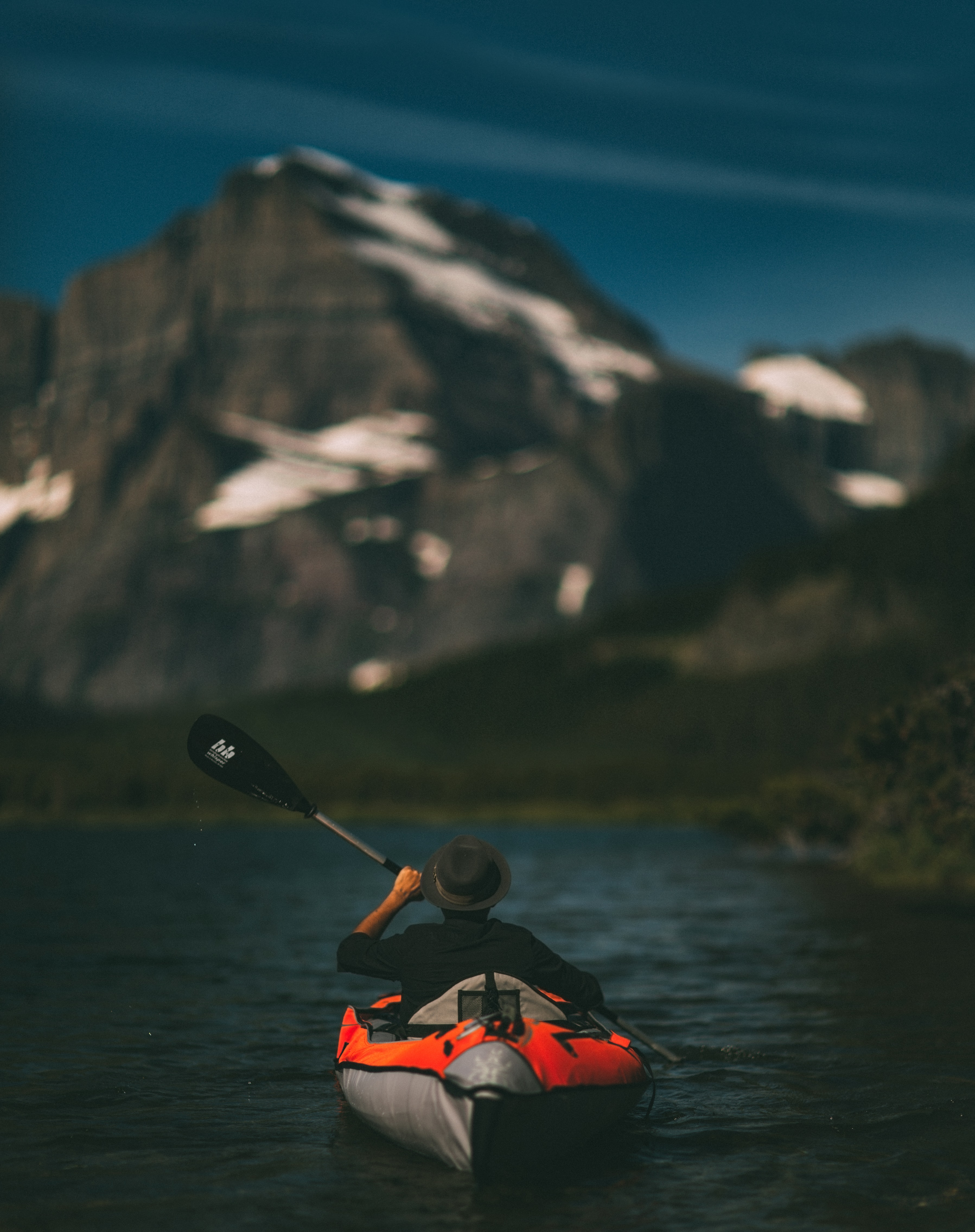 A man wearing a hat paddling in a blow up orange canoe in Swiftcurrent Lake